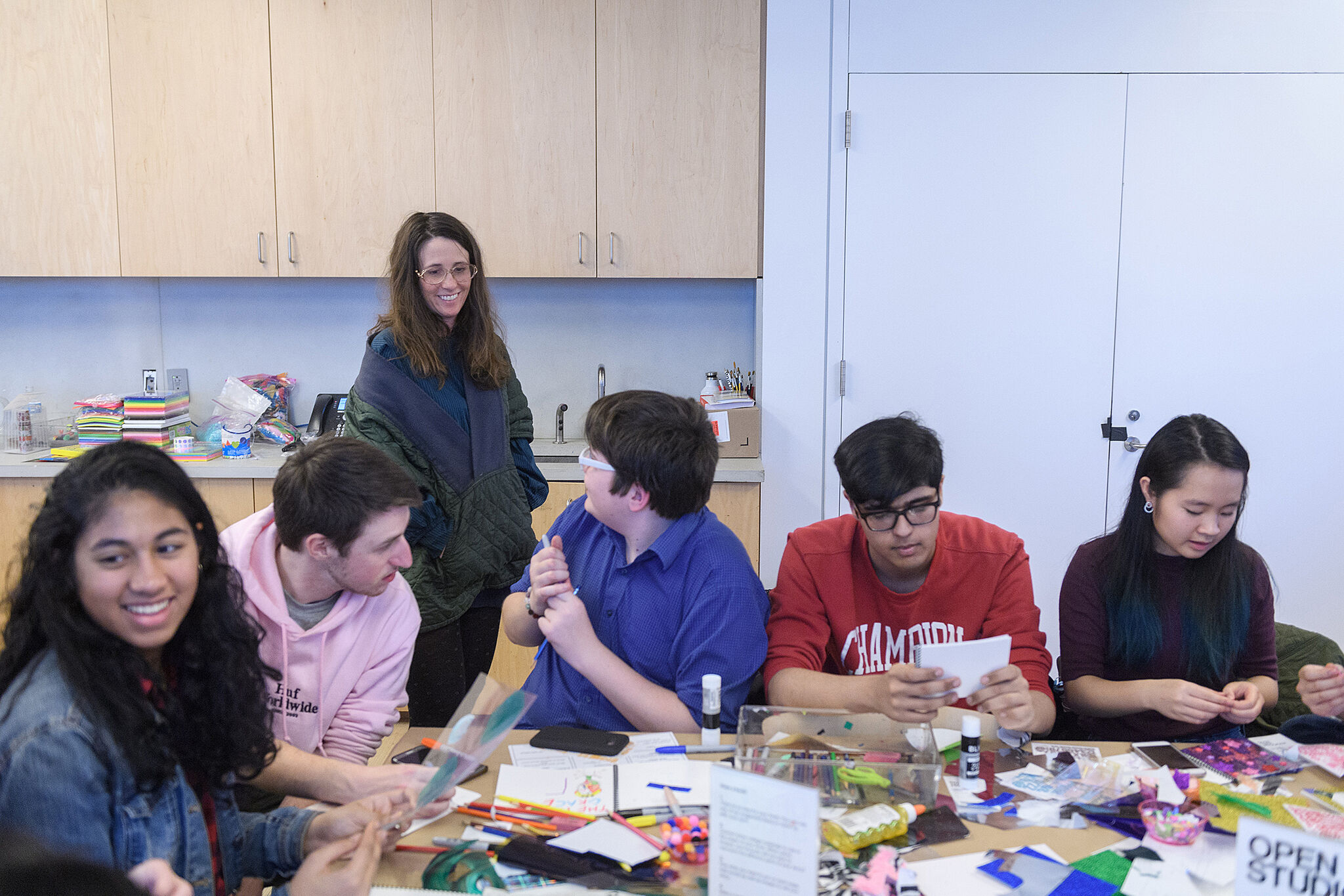 A photo of a group of teens working on art projects at a table, while Laura Owens smiles and talks with one of them.