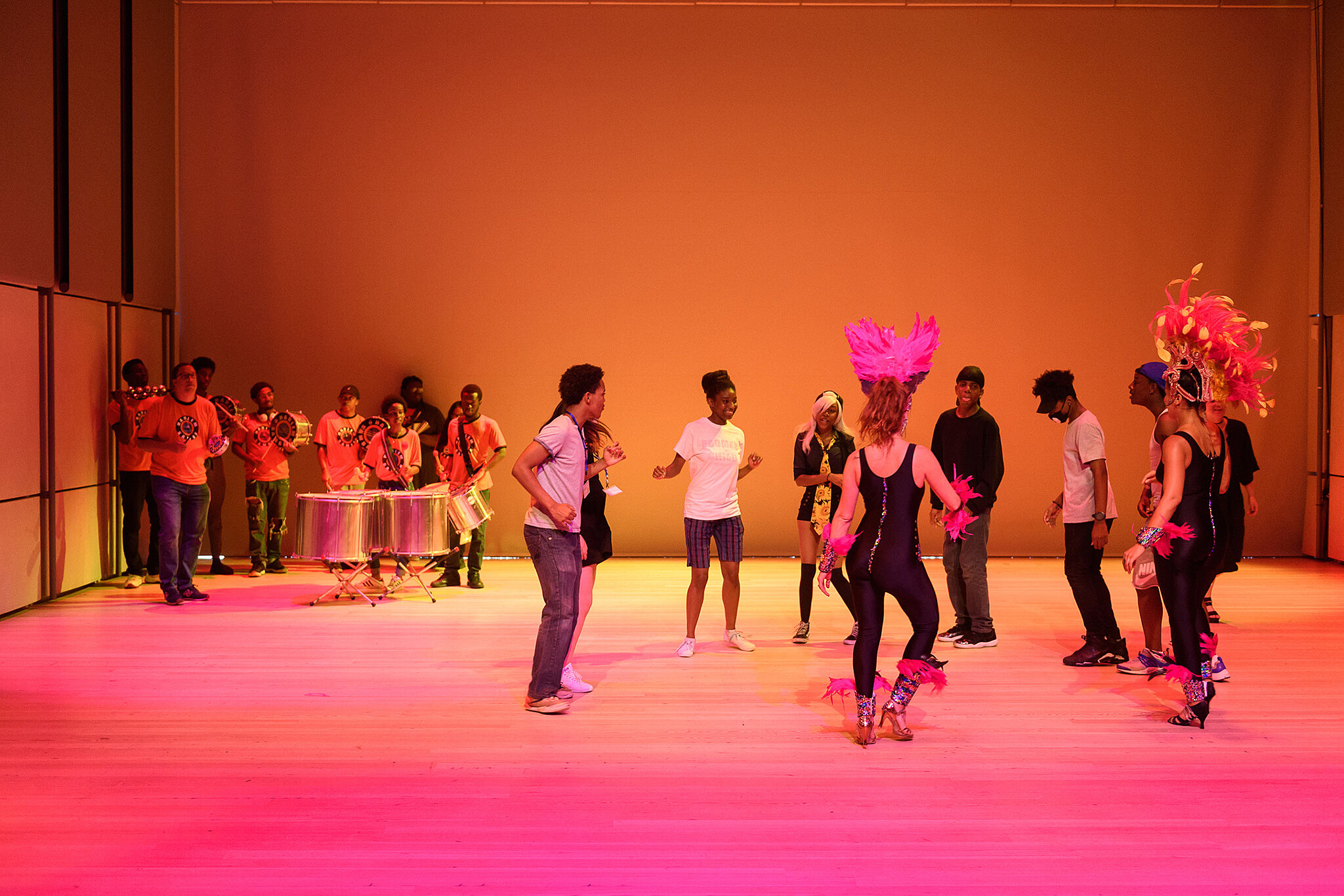 A photo of a teens engaging with costumed dancers in a brightly colored room, while a band plays in the corner.