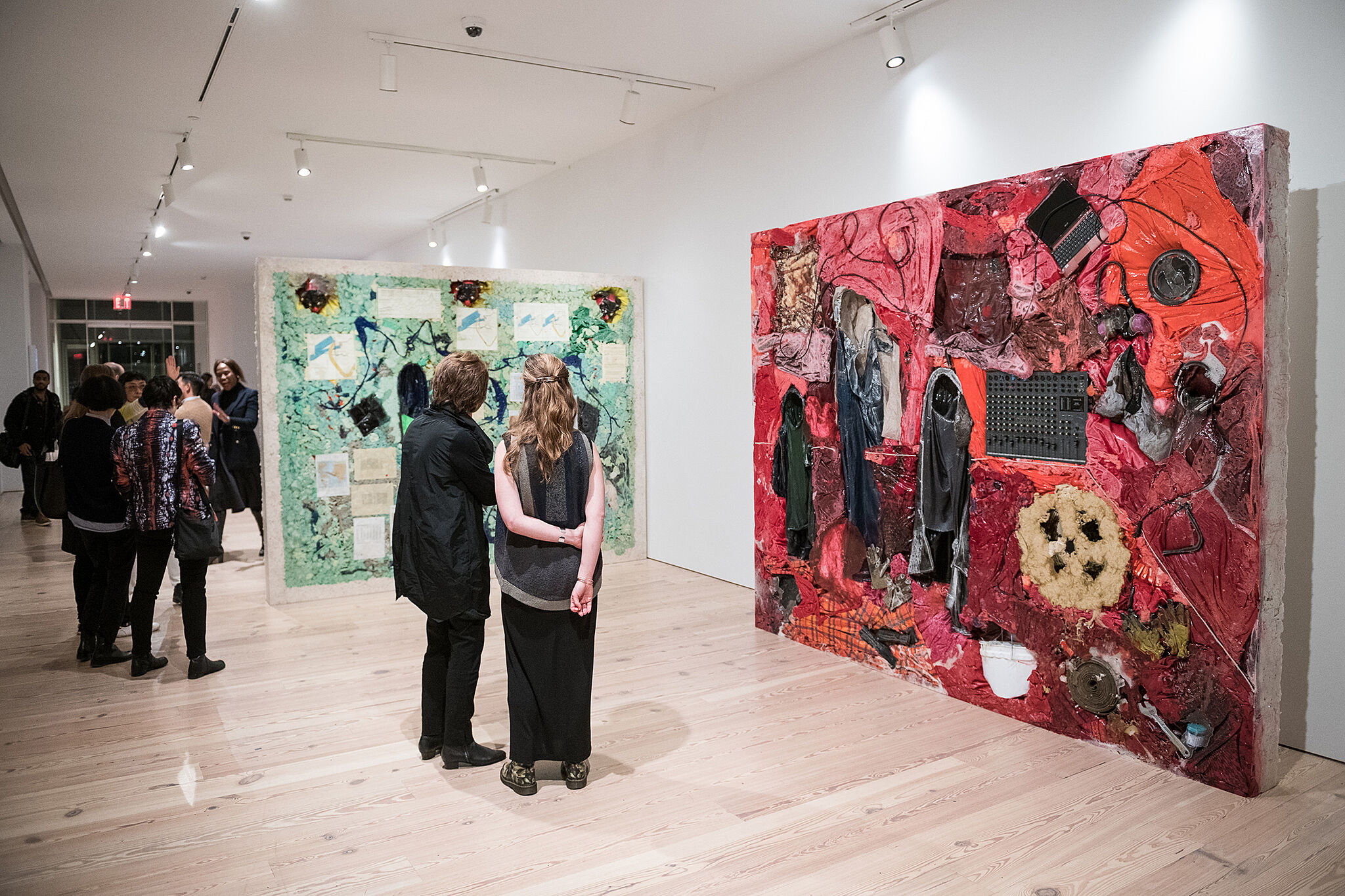Visitors look at two large-scale artworks by Kevin Beasley