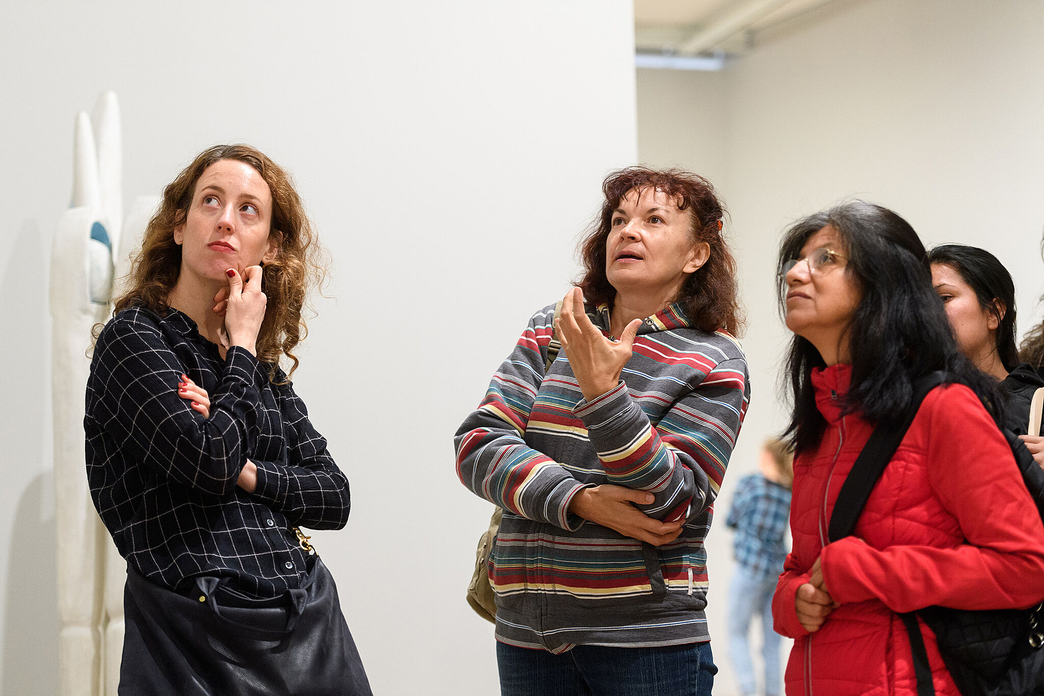 A photo of three visitors looking up at a piece of art.