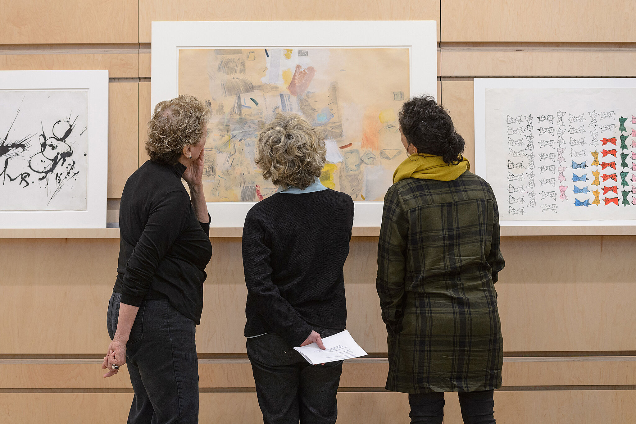Three people examine an artwork, which hangs on a wall.