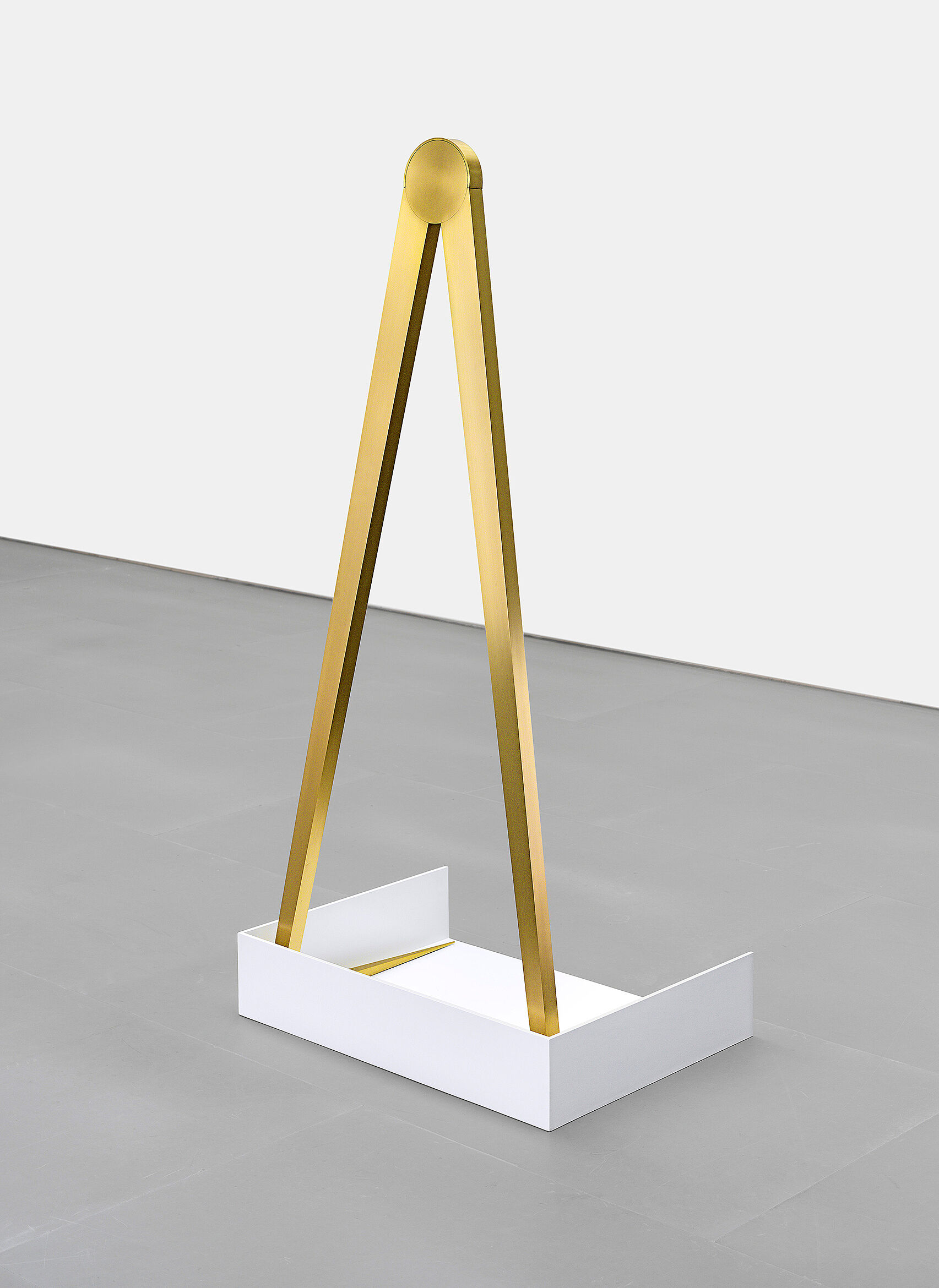 A sculpture featuring a bronze triangle shape, sitting in a white box
