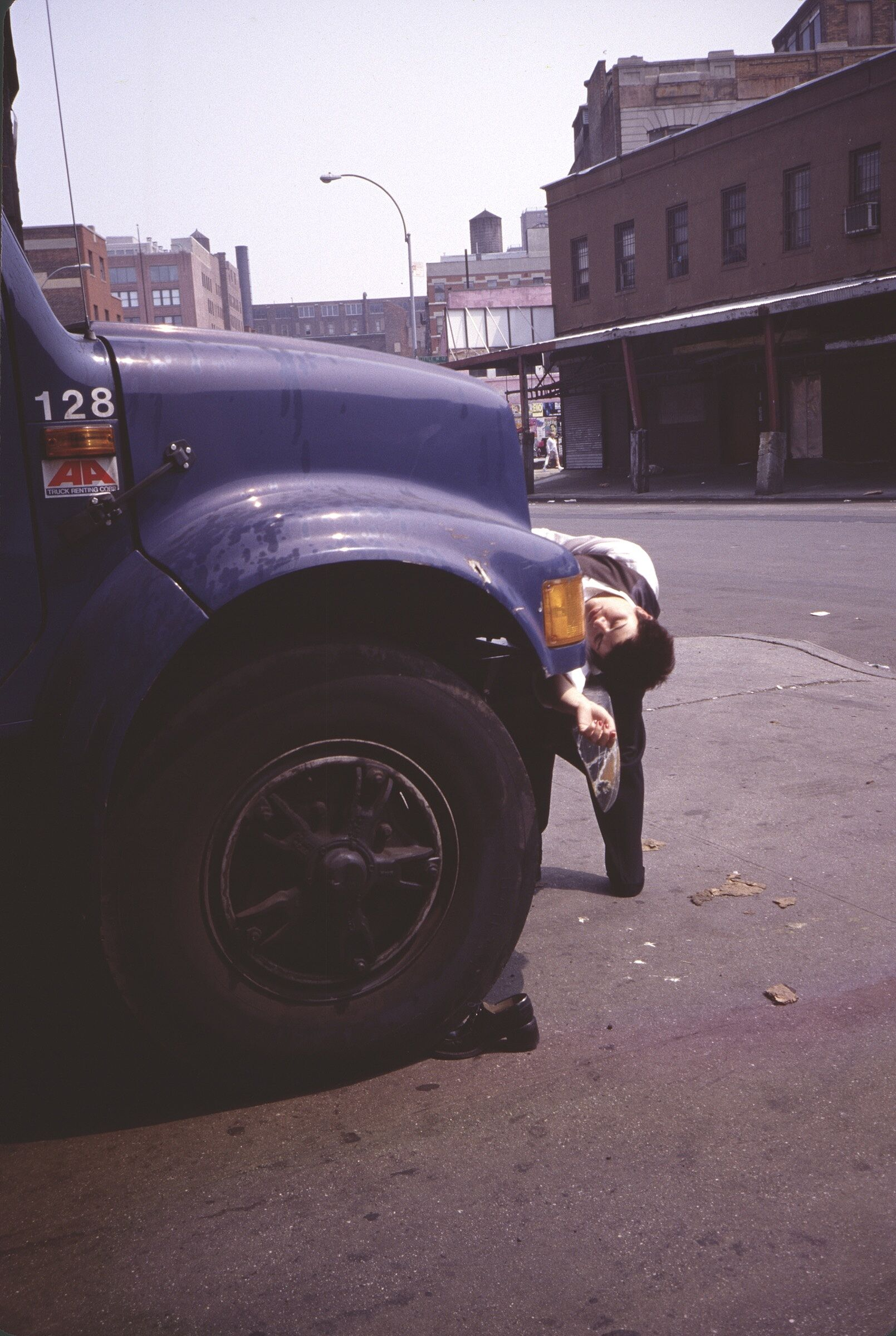 A film still of a person bending backward behind a blue truck.