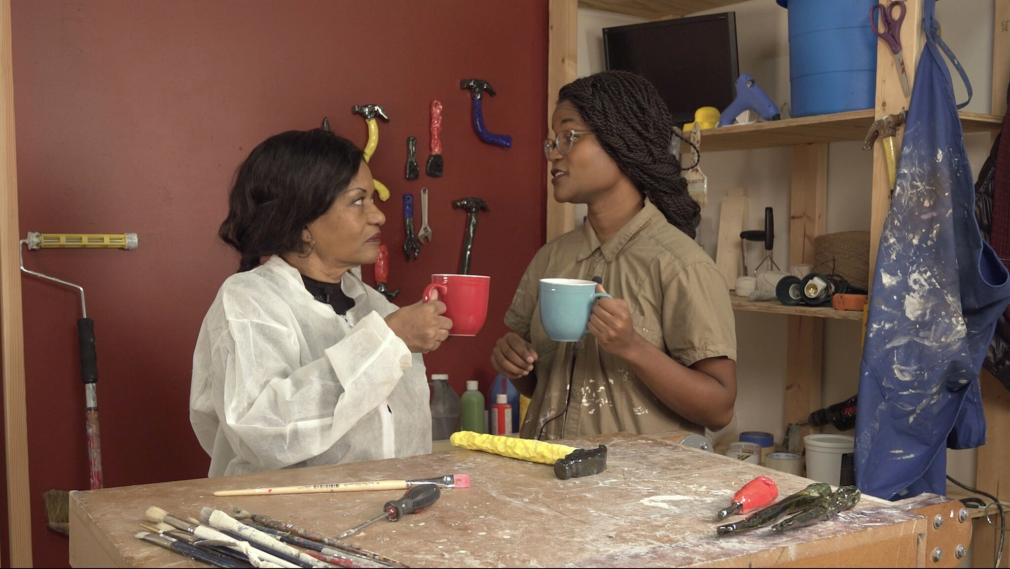 A still of two people in a restoration workspace holding coffee mugs and looking at each other.