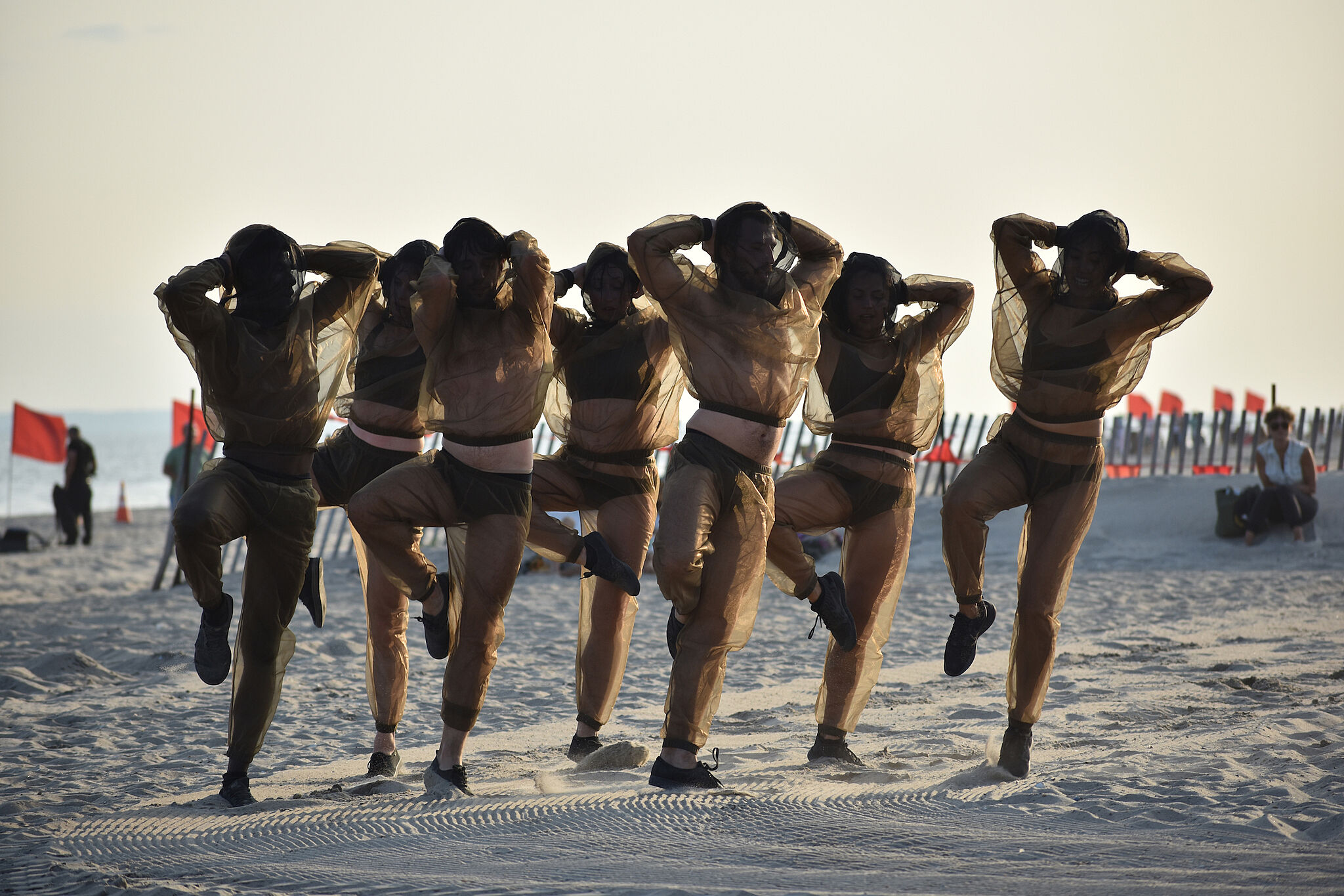 A photo of seven people posed in performance on a beach.
