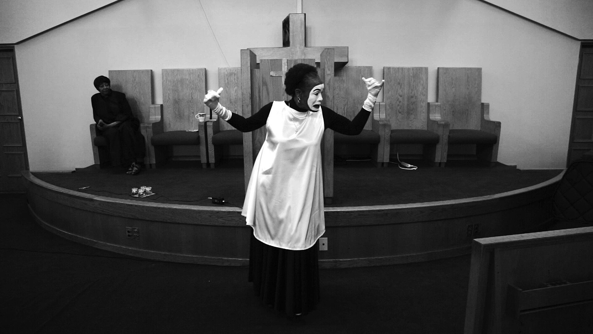 A black-and-white still of a woman in a white robe and mask in front of a  platform featuring Christian crosses.