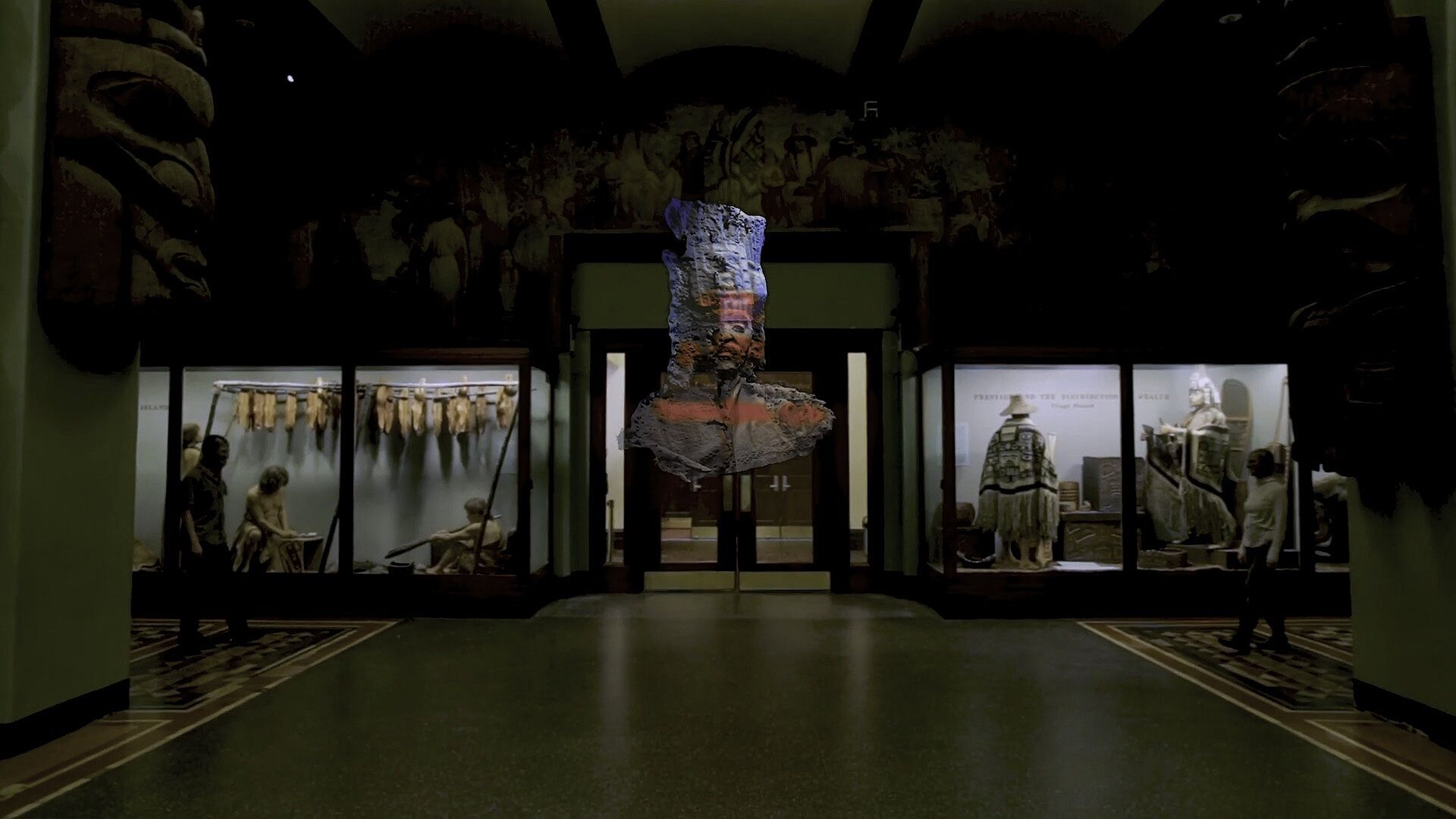 A view of an installation of a sculpture in the center of a room with other glass encasements of cultural objects.