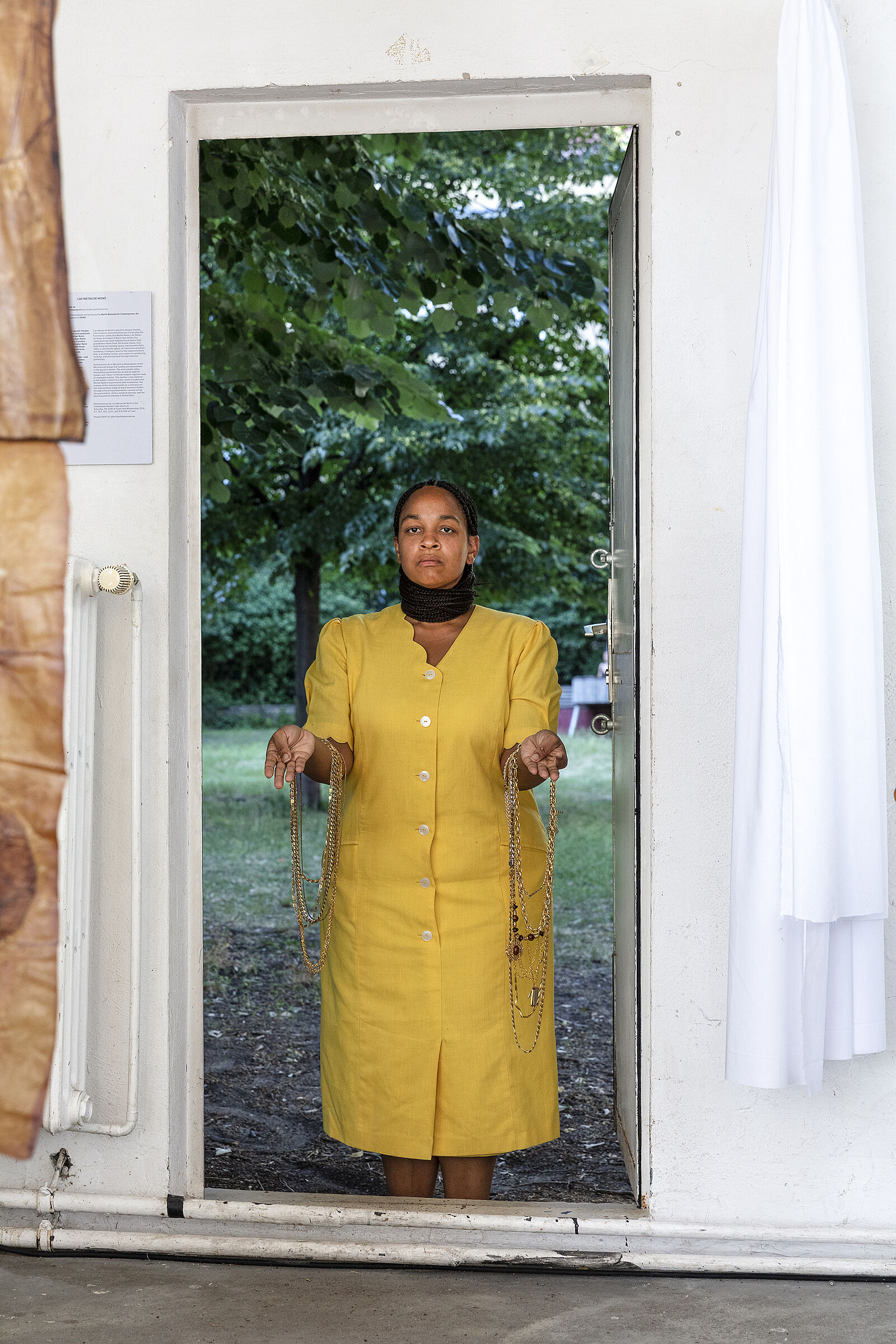 A view of a woman in a yellow dress standing in a doorway that leads to a yard.
