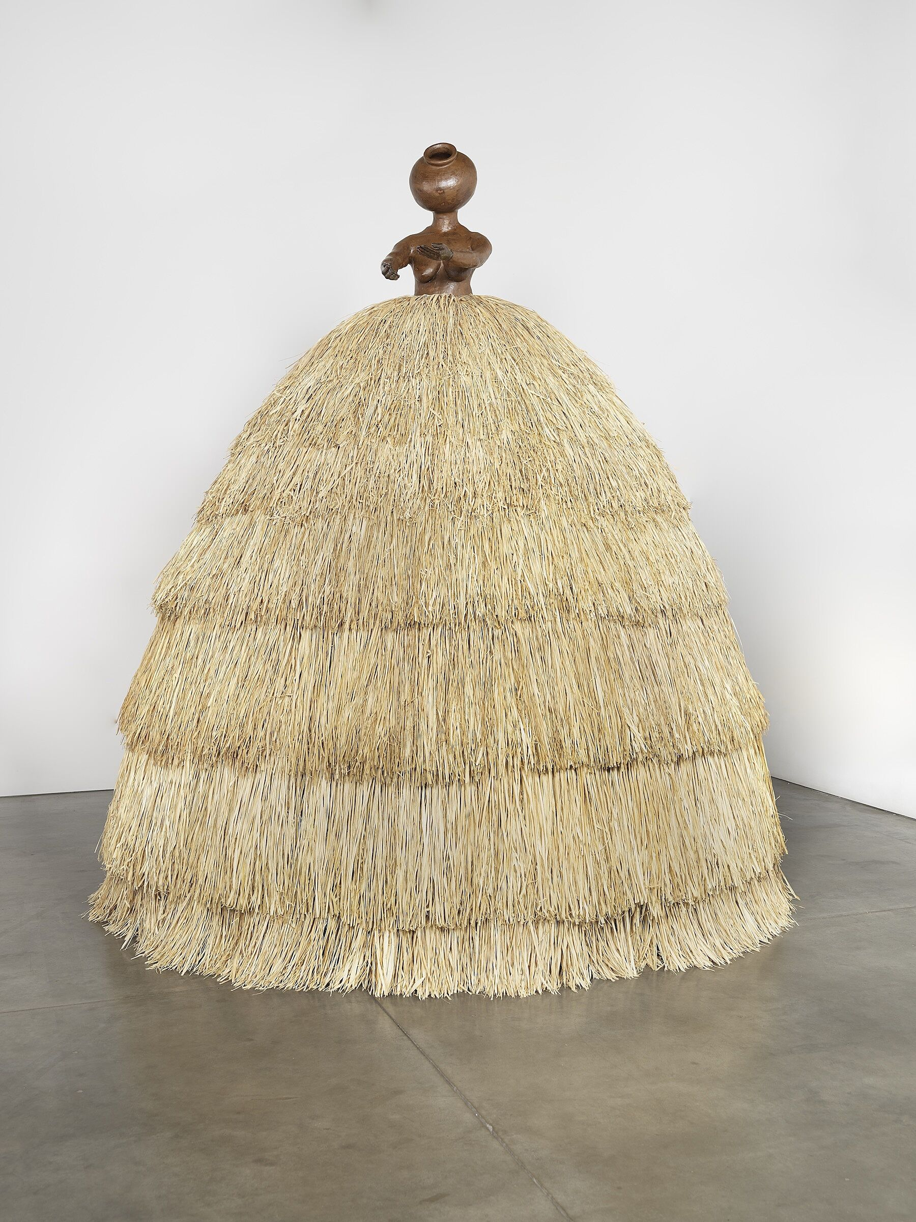 A sculpture of a small stone figure wearing a wide straw-like skirt.