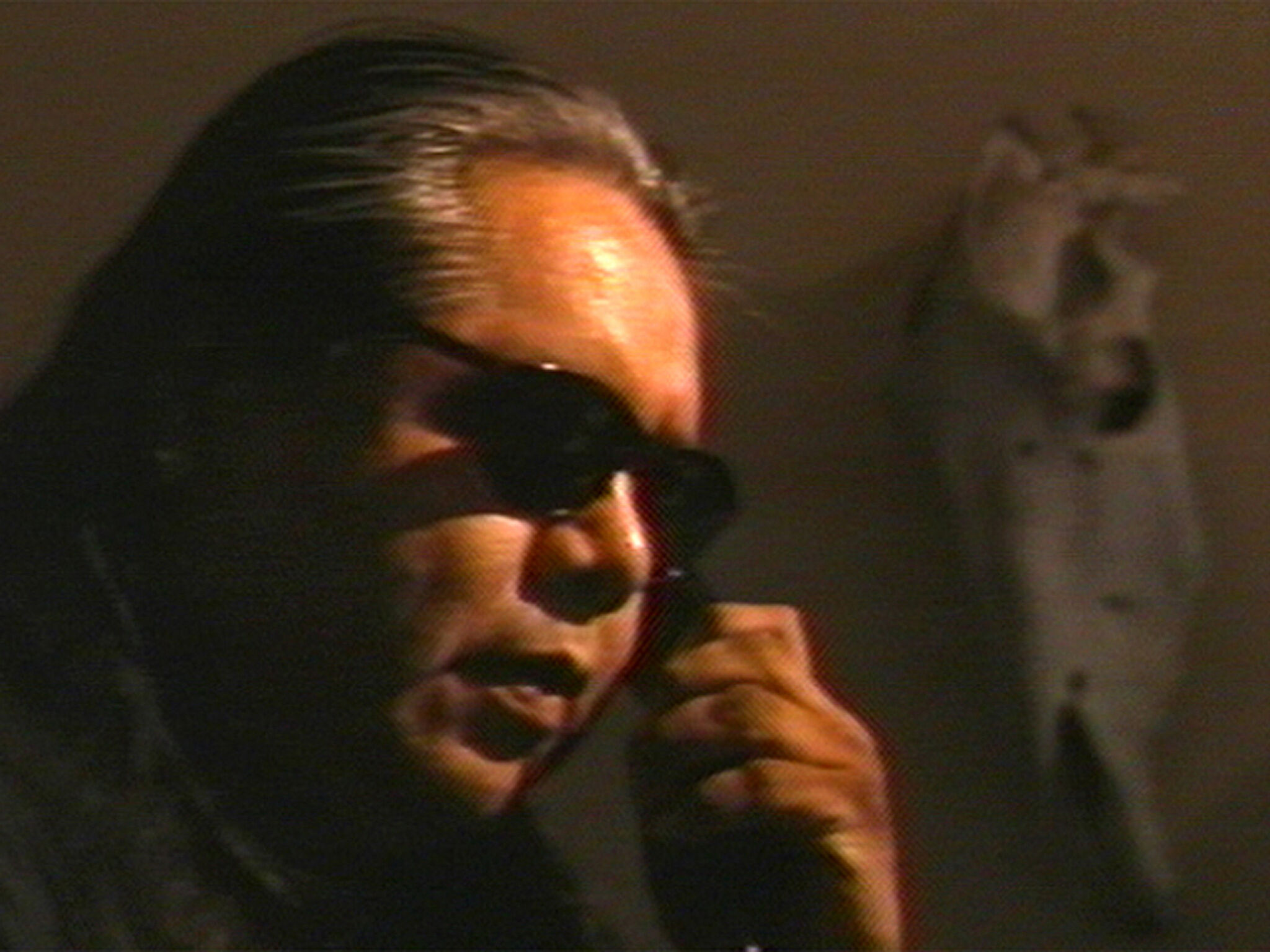 A close-up video still of a man wearing sunglasses.