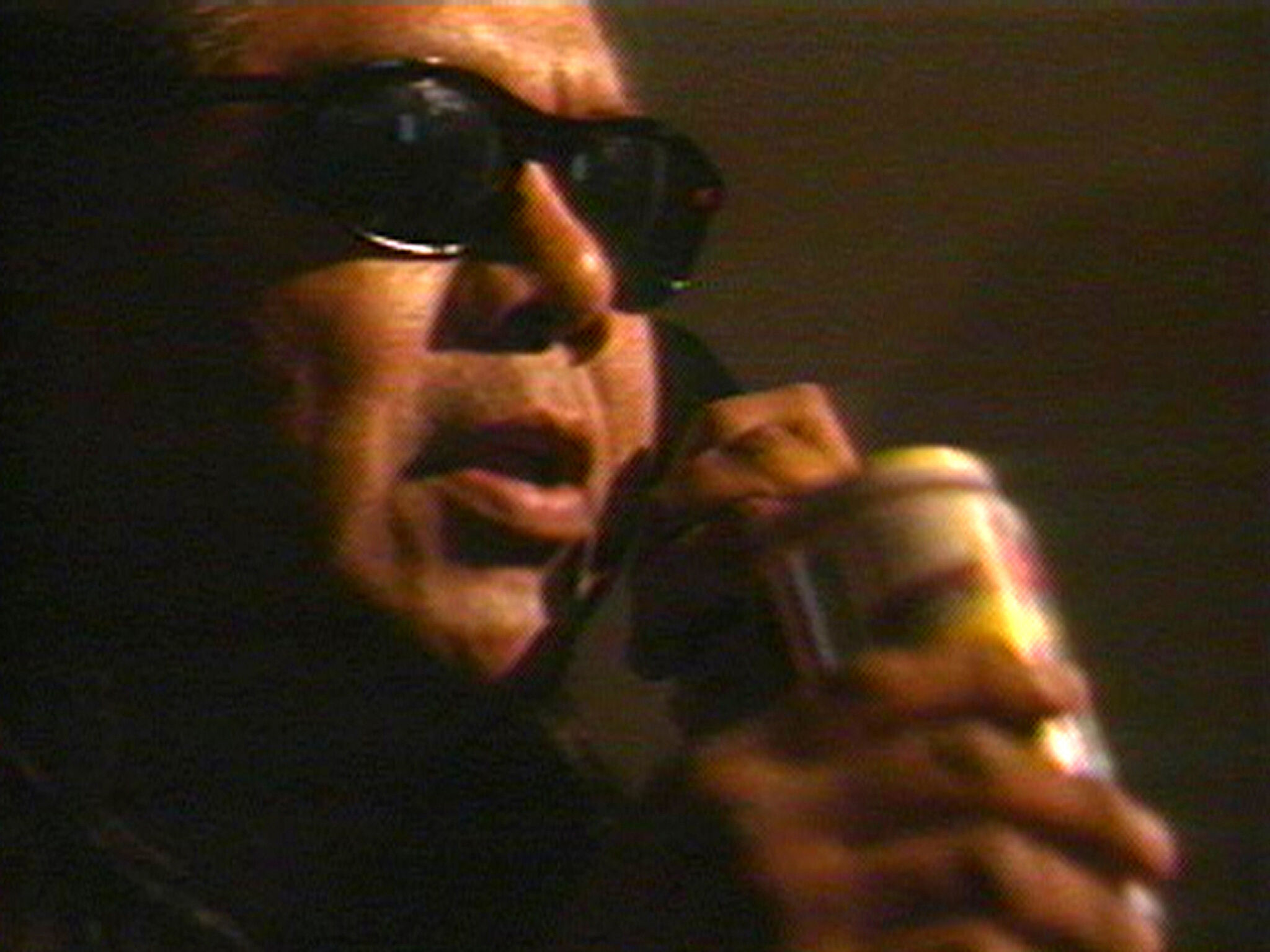 A close-up video still of a man wearing sunglasses, holding a can and a phone.
