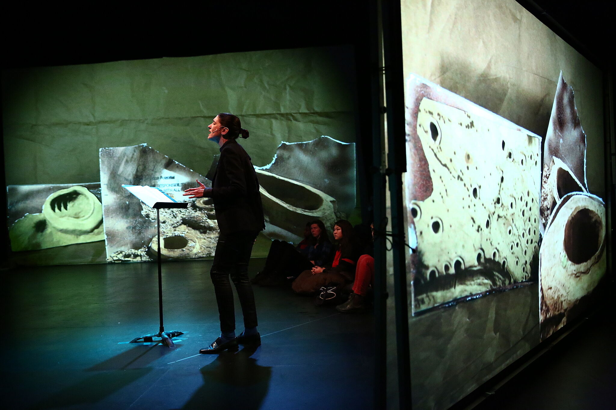 A photo of a person performing with a music stand surrounded by a multimedia performance.