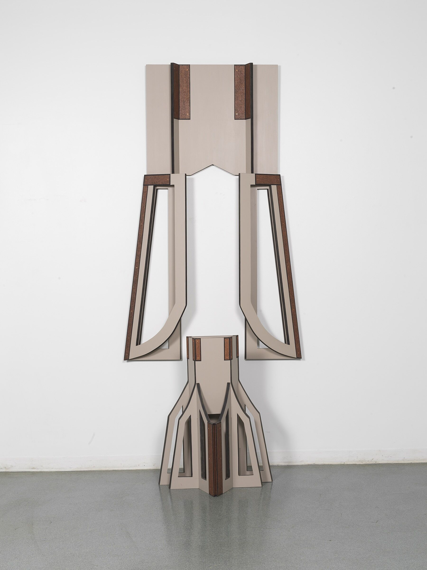 A beige, geometric sculpture with elements both hanging on the wall and on the floor.