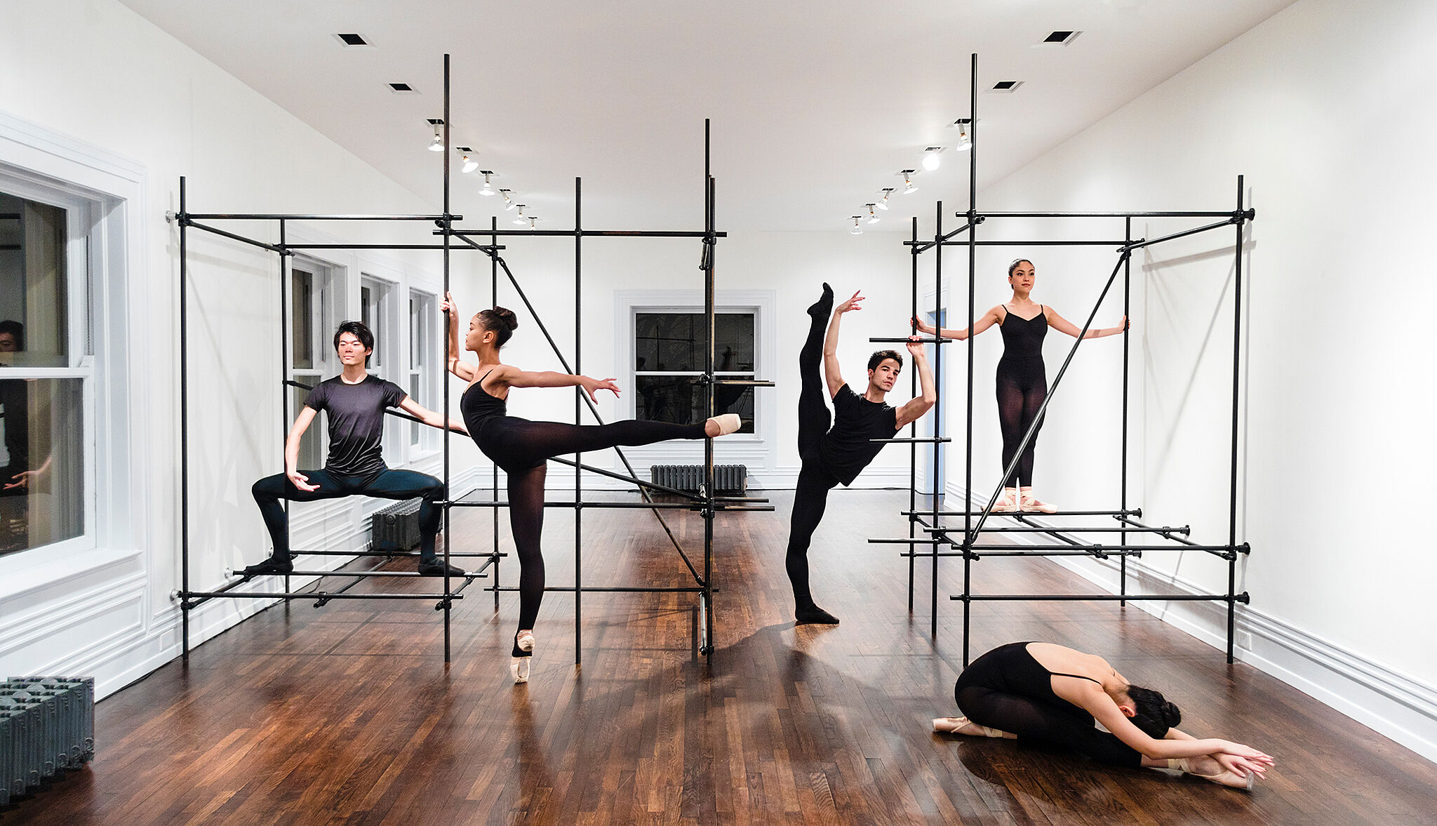 Four dancers pose in a rehearsal space with metal bar structures.