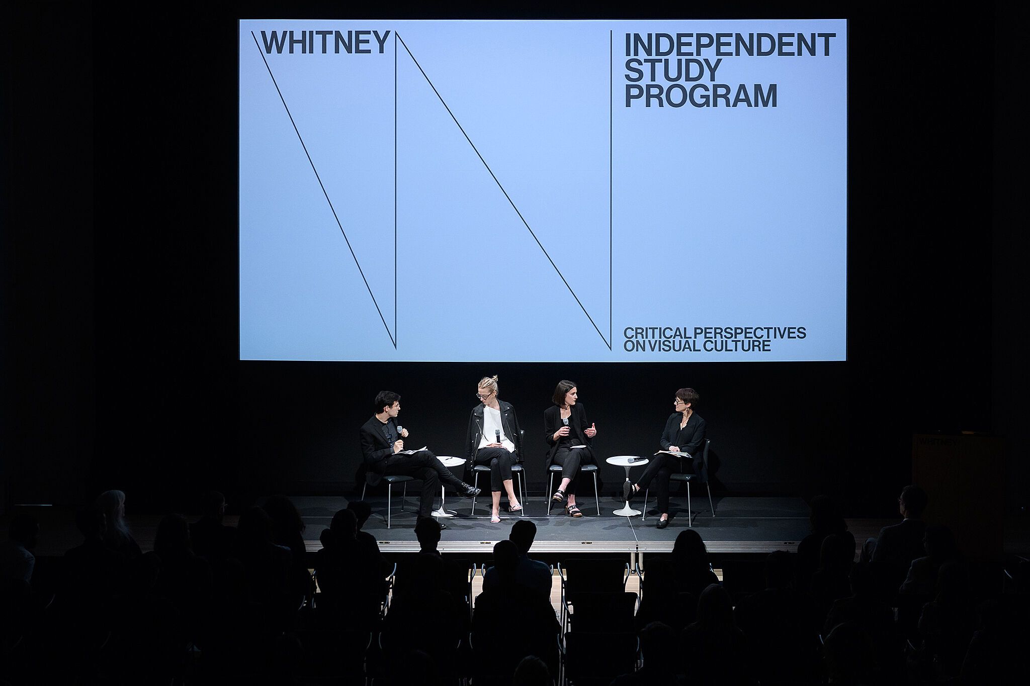 Four people sit on a stage, with a screen lit up behind them with the Whitney Museum logo