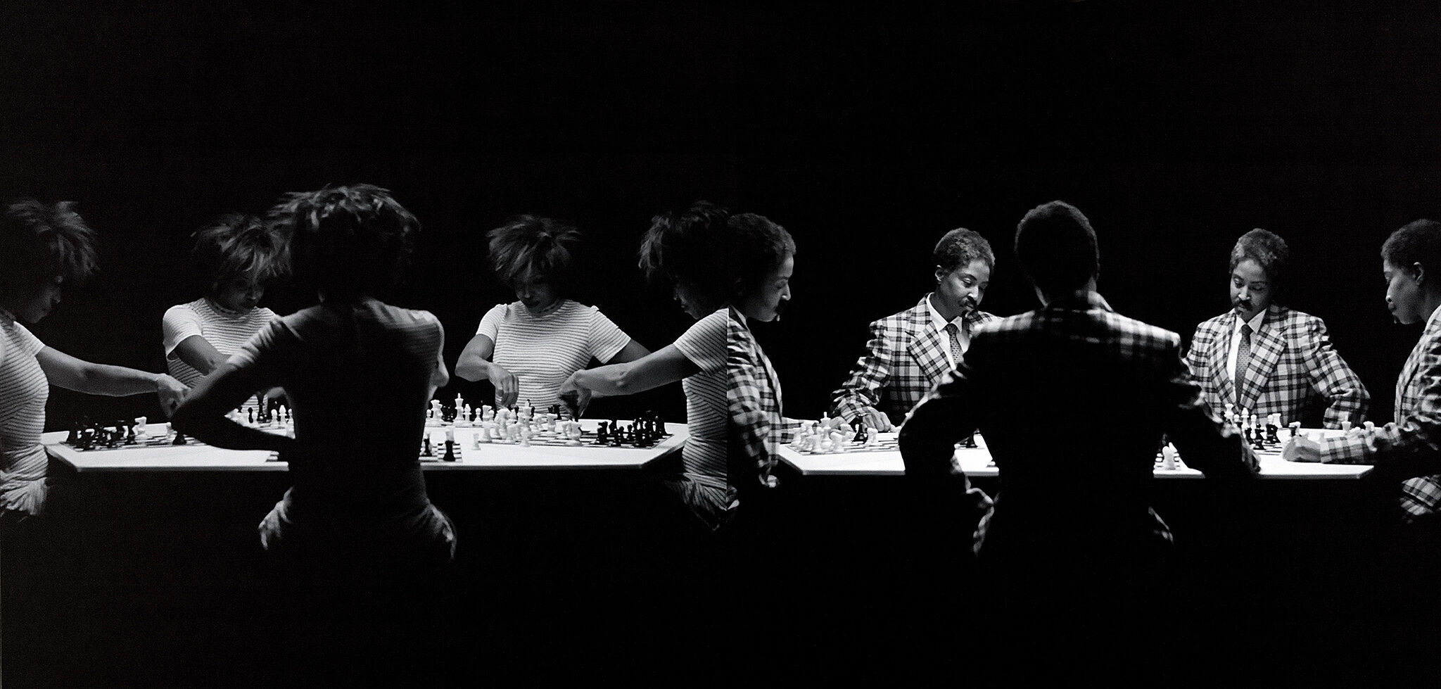 A high contrast photograph of people playing chess.