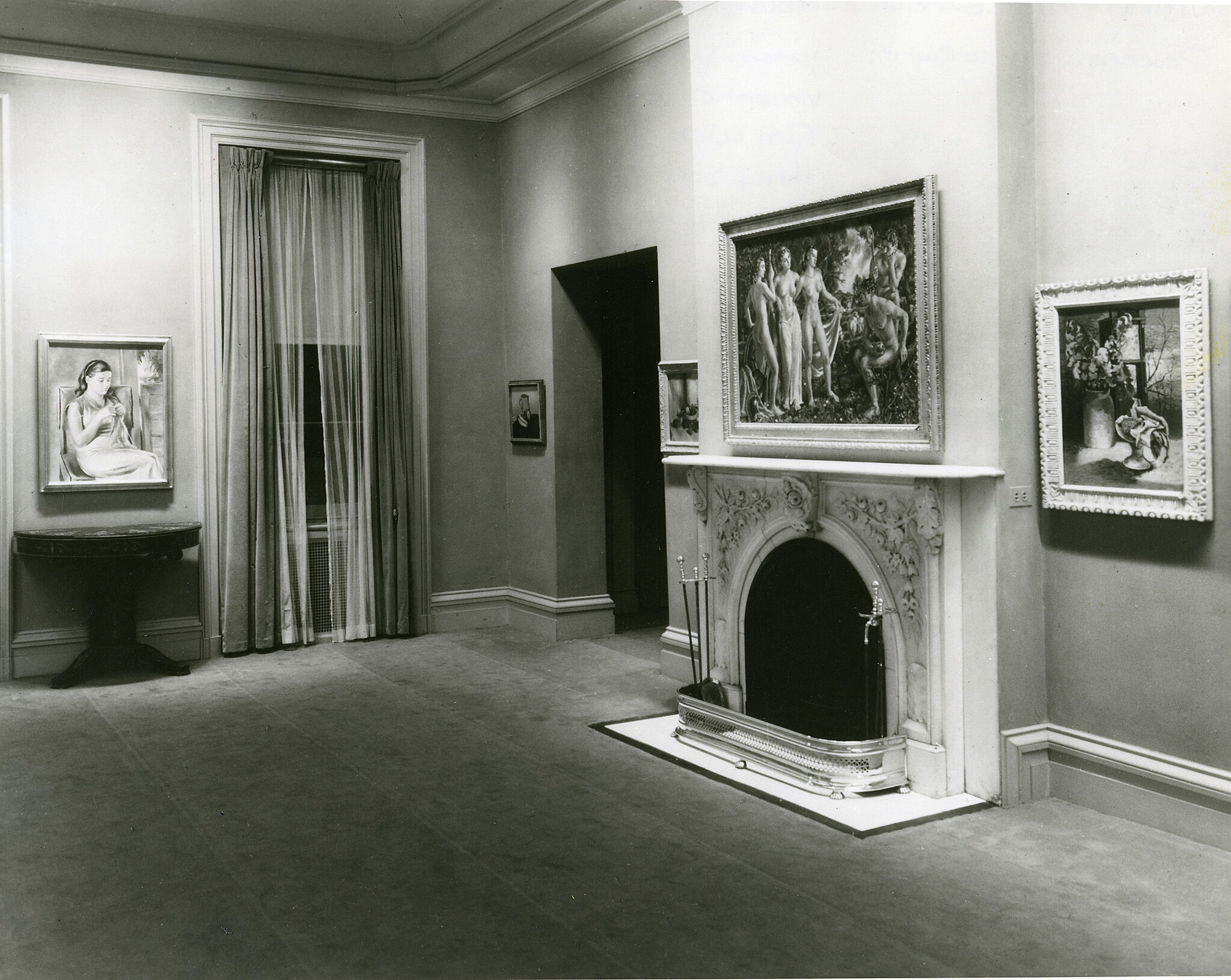 Several paintings hang on wall in a room with a fireplace