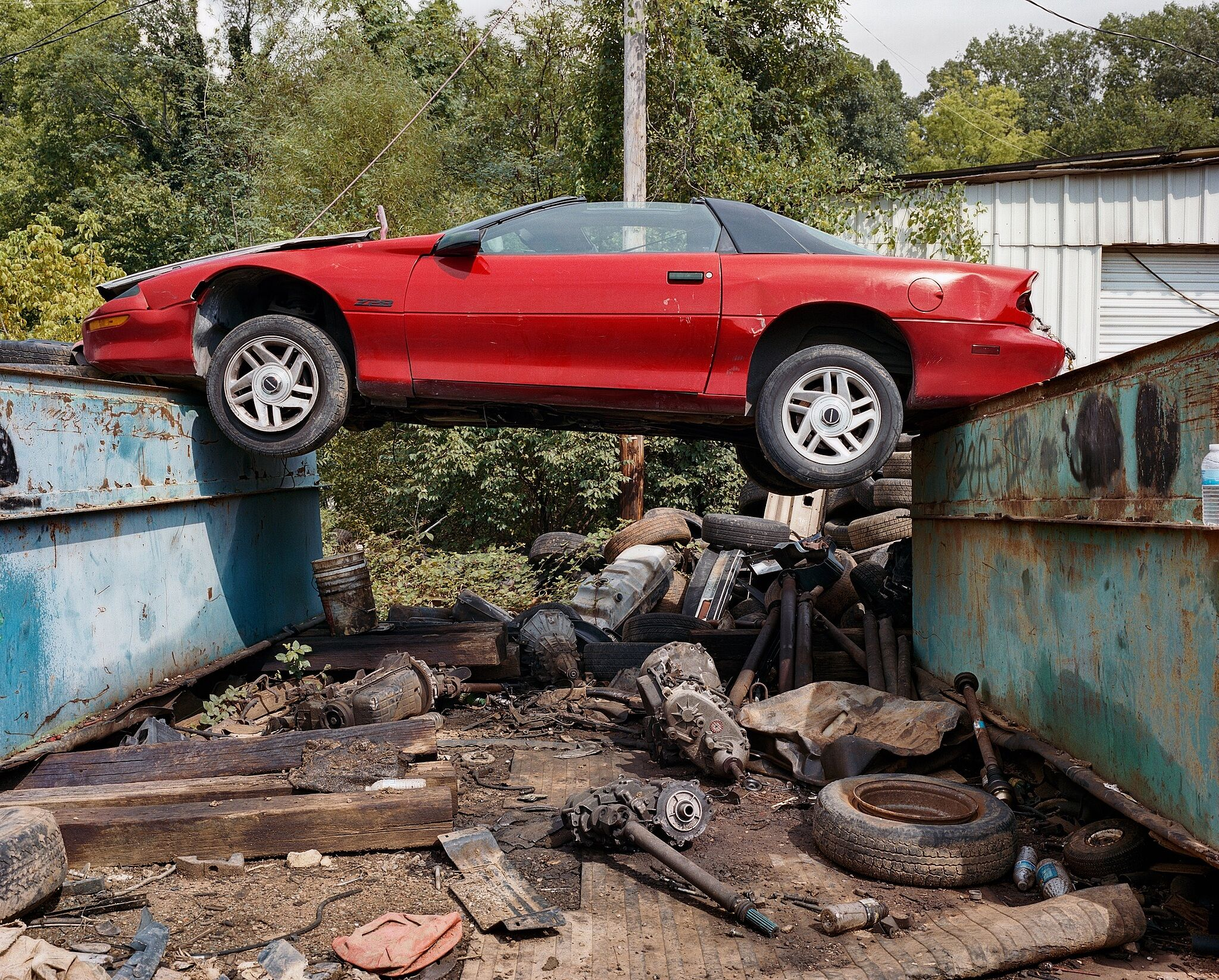 A red Camaro suspended on top of two garbage dumps in a wooded area.