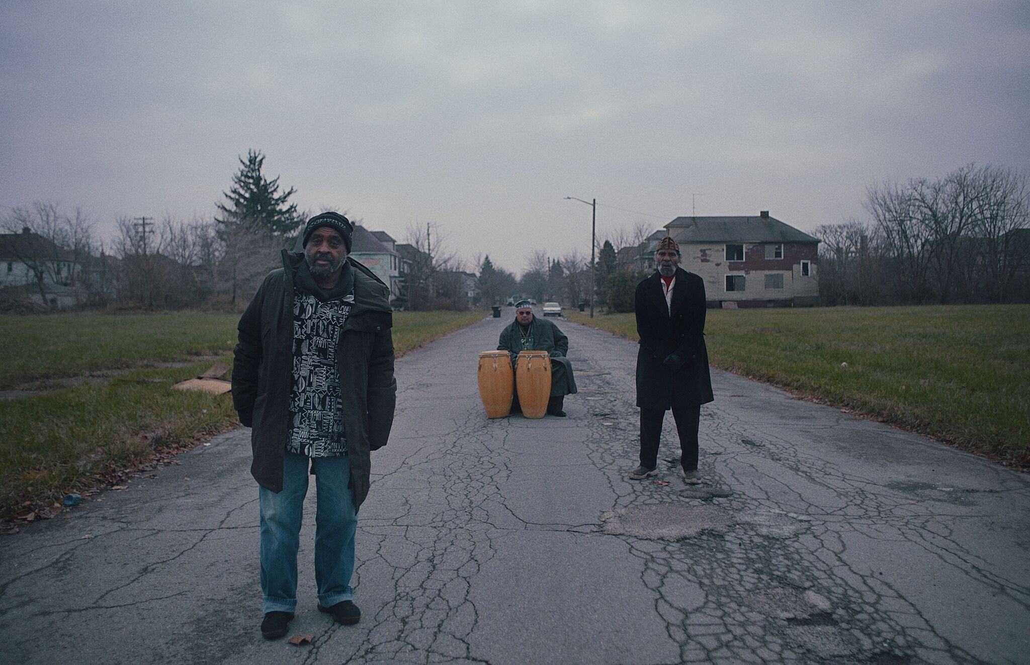 A video still of the people in the middle of a road, two standing and one sitting behind two large drums.