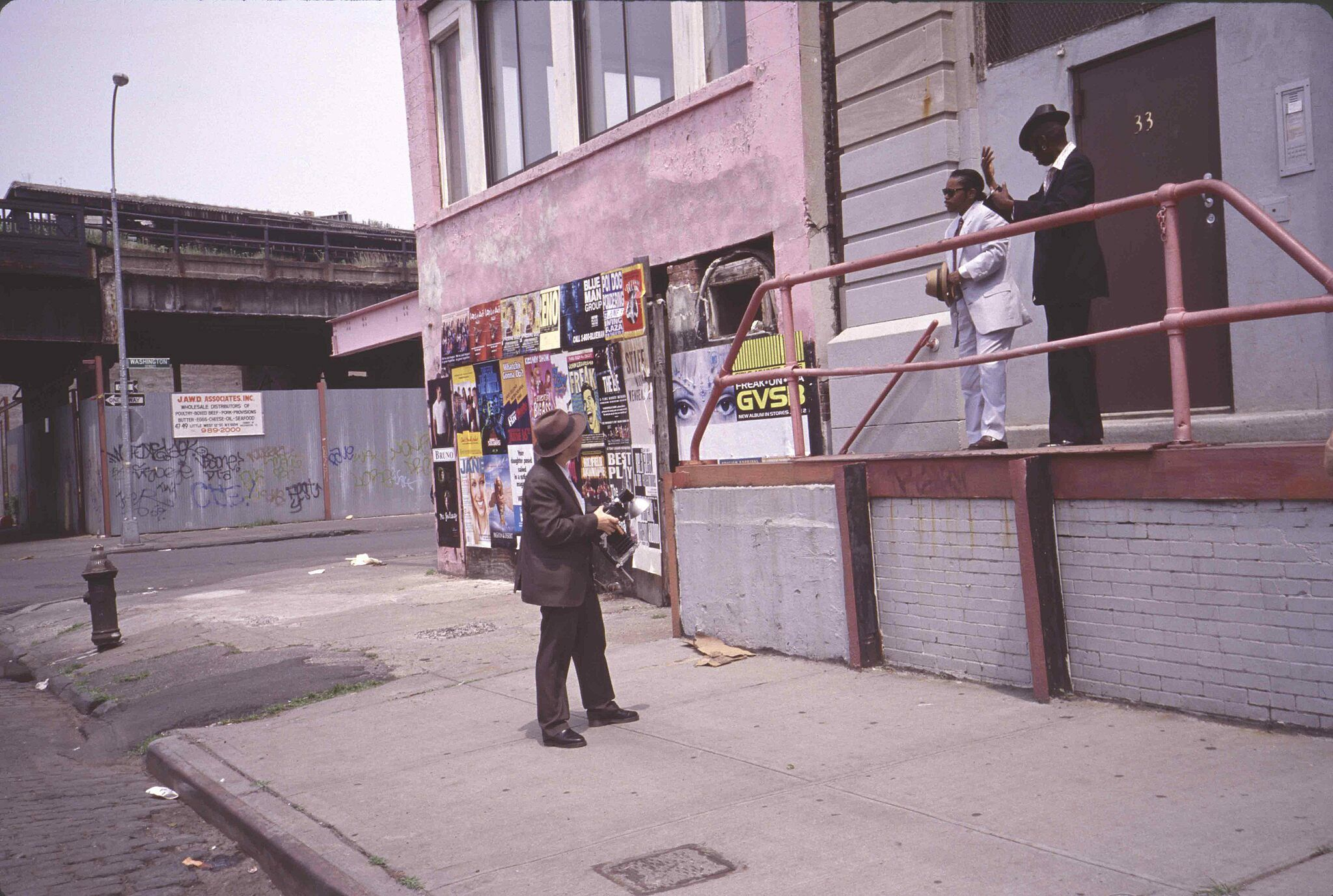 A photograph of two men on a platform looking at a man below them on the street holding a camera.