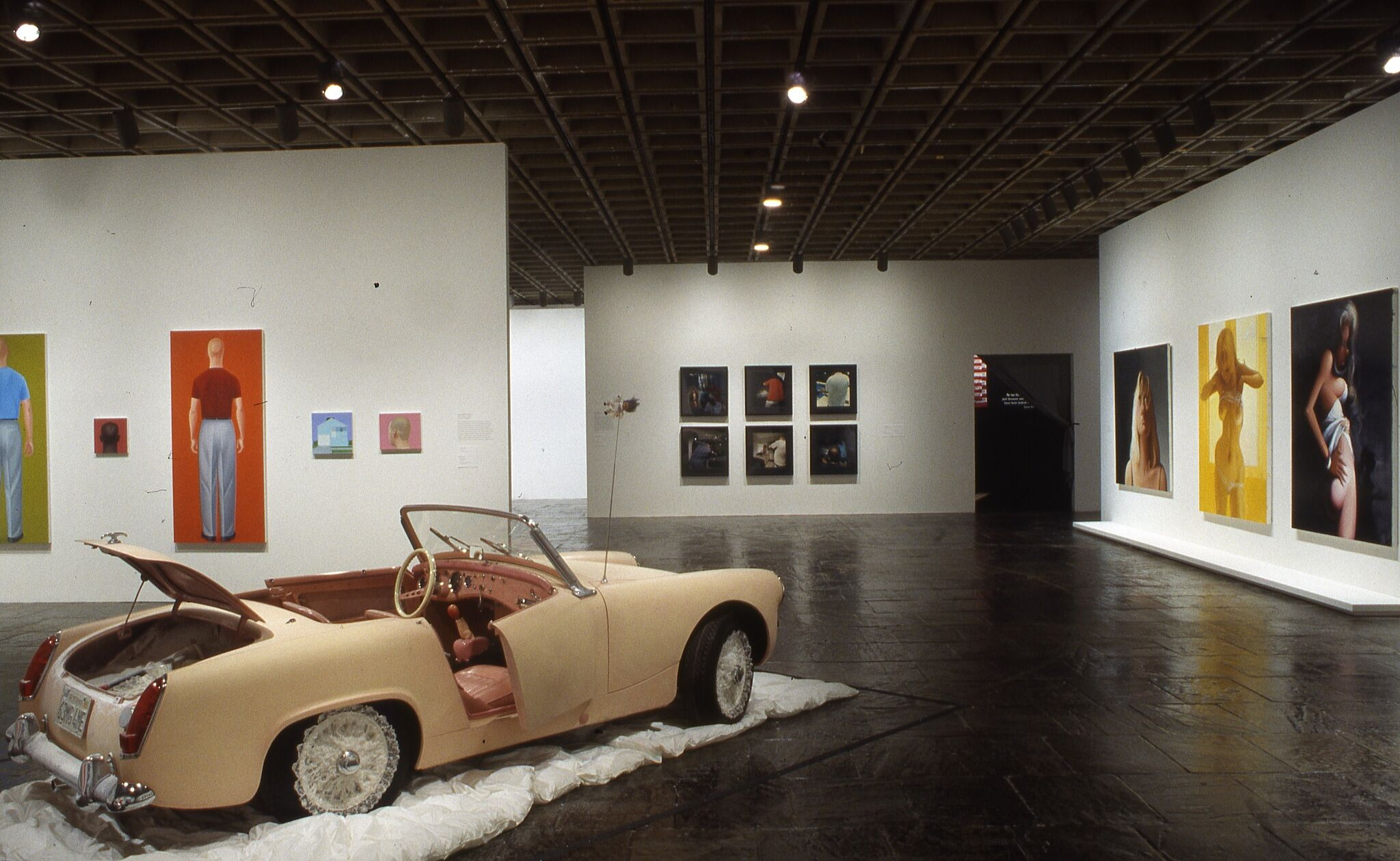 A gallery filled with works of art on the walls and a sculpture of a car.