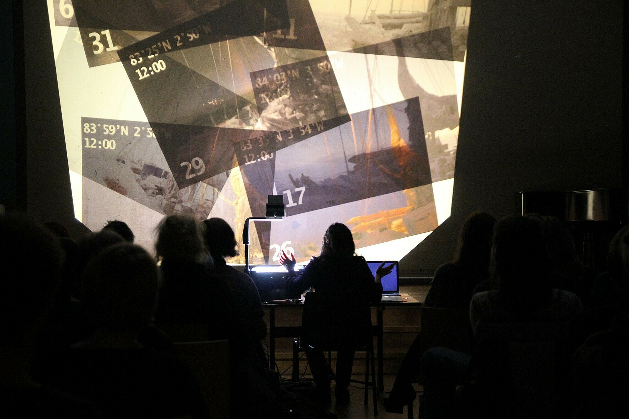 A performance view of a person sitting in front of a wall with projected images.