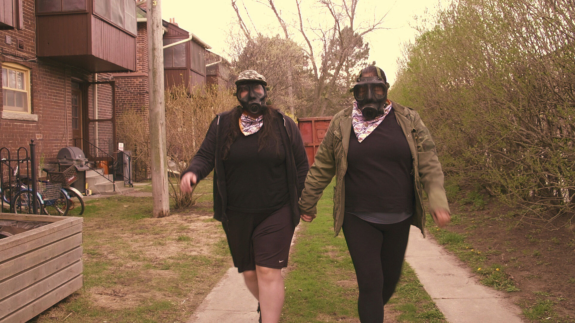 A video still of two people walking and wearing gas masks.