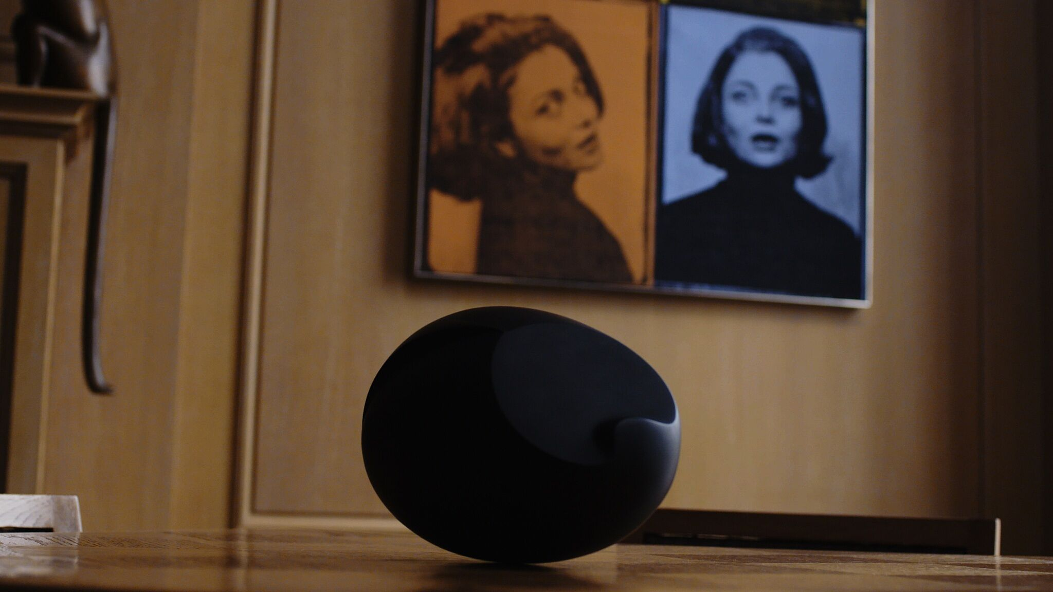 A video still of a round object on the floor in front of a wall with portraits hanging on it.