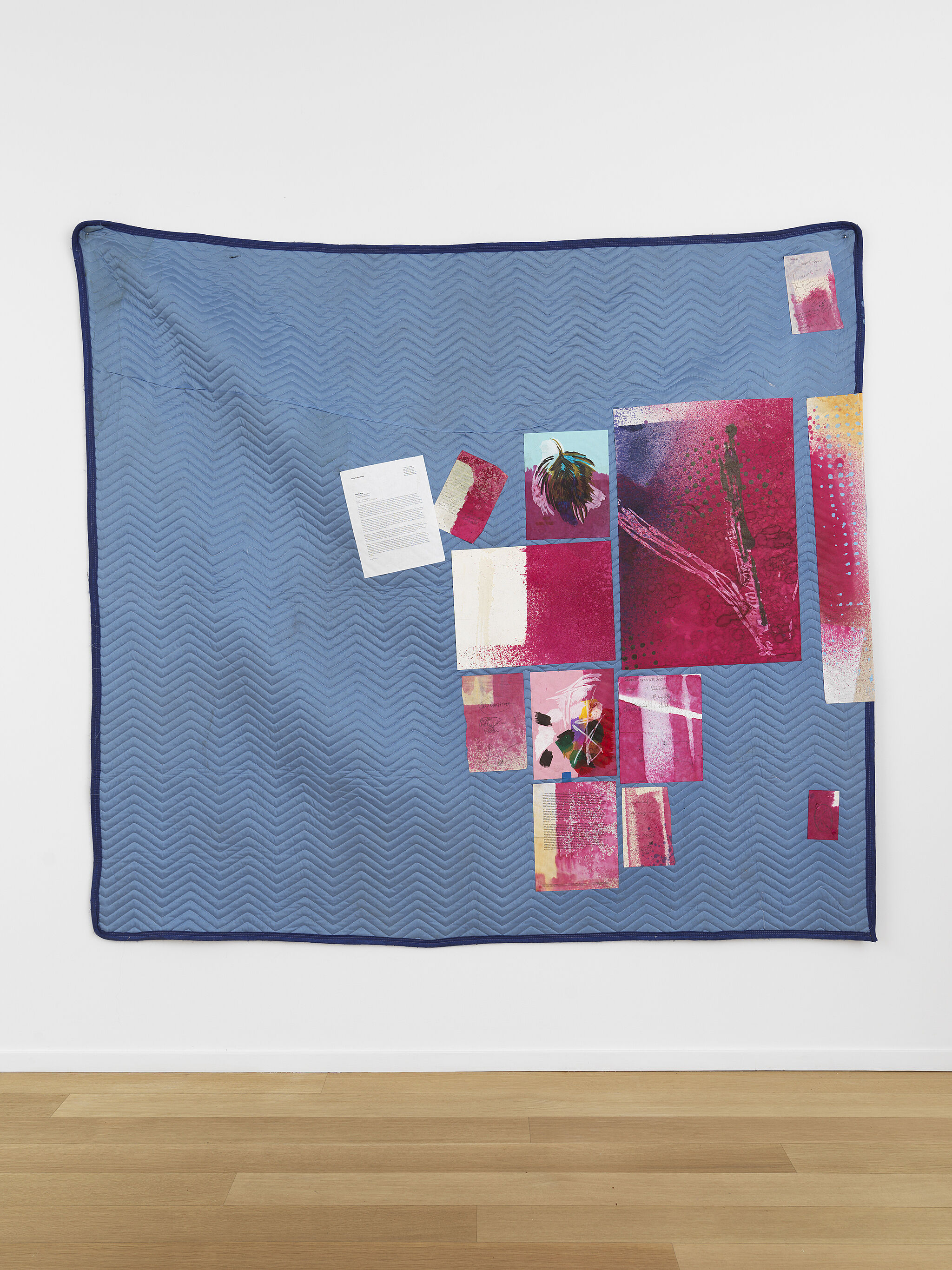 A moving blanket hanging on a wall with paper works attached.