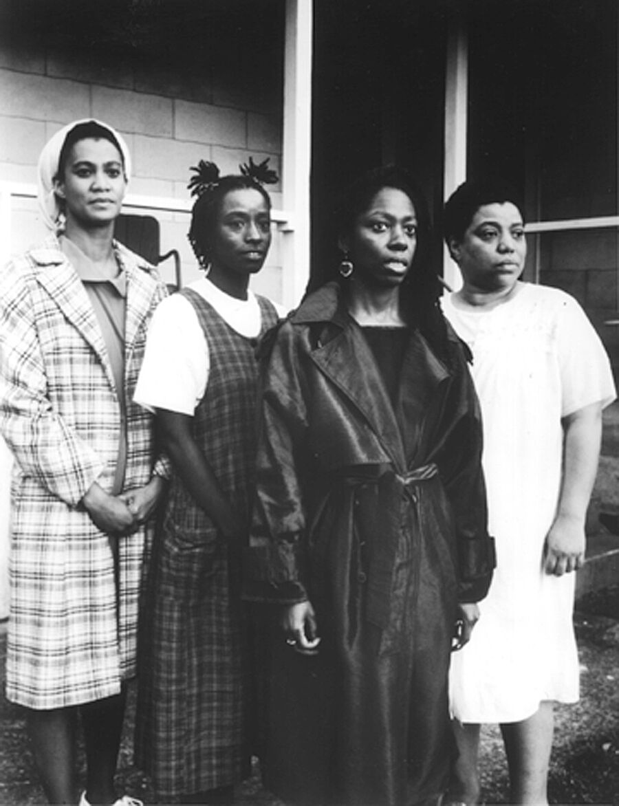 A film still of 4 women staring into the distance.