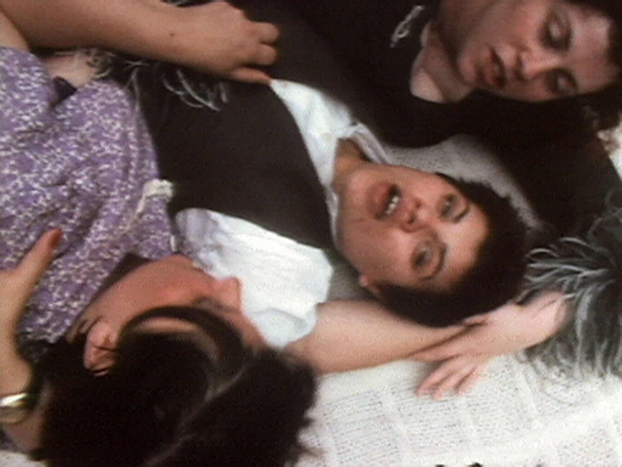 A film still of three people laying on a blanket.