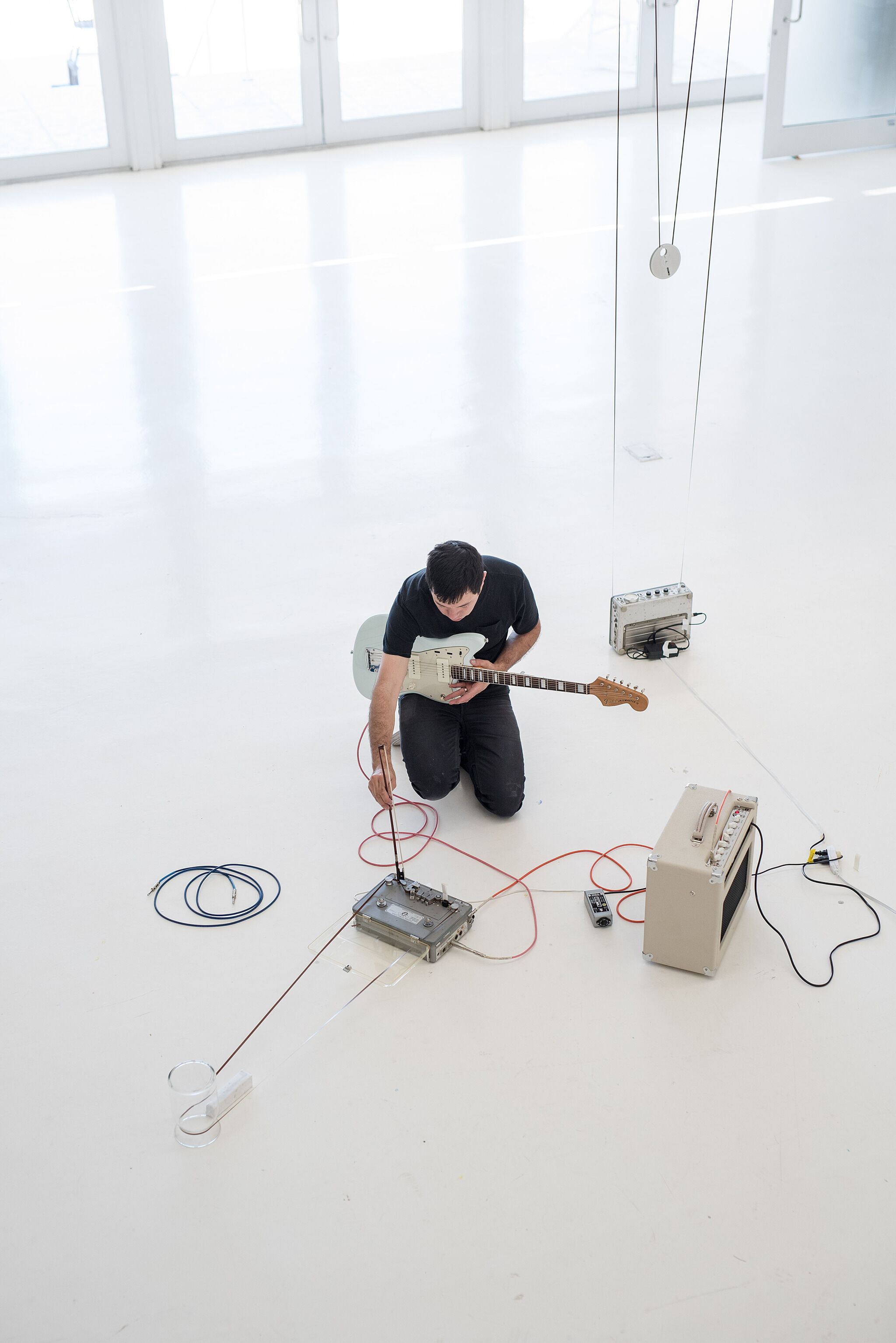 An aerial view of an artist generating a sound installation with a guitar.