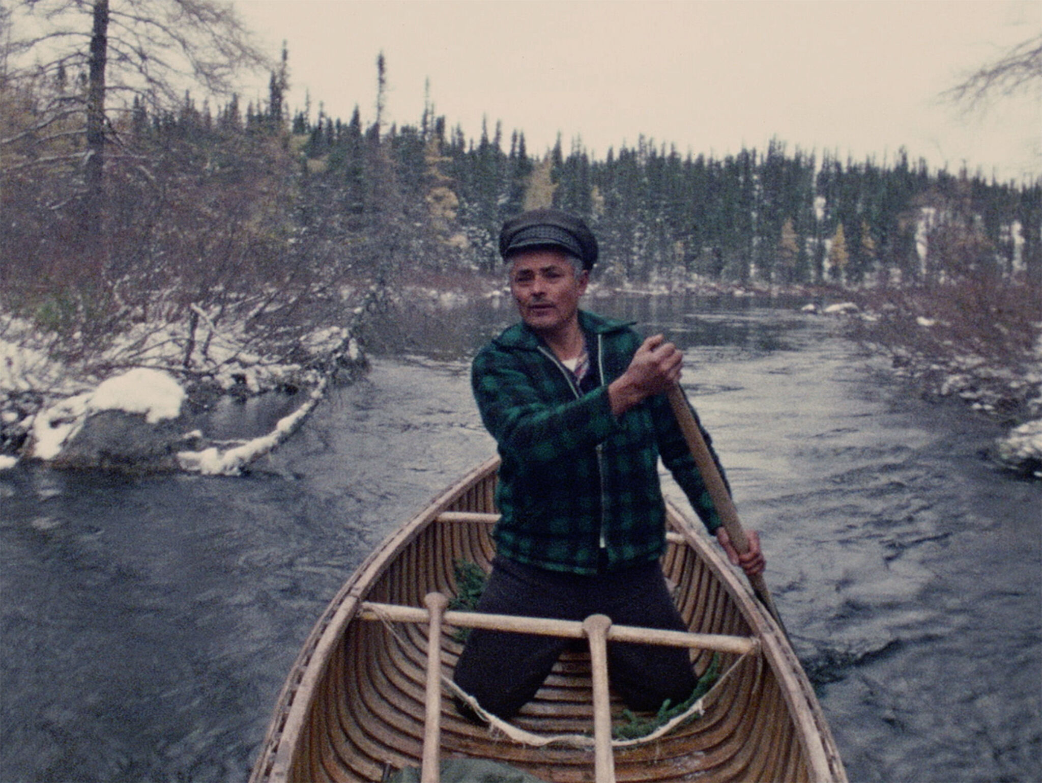 A man standing in a boat paddling.