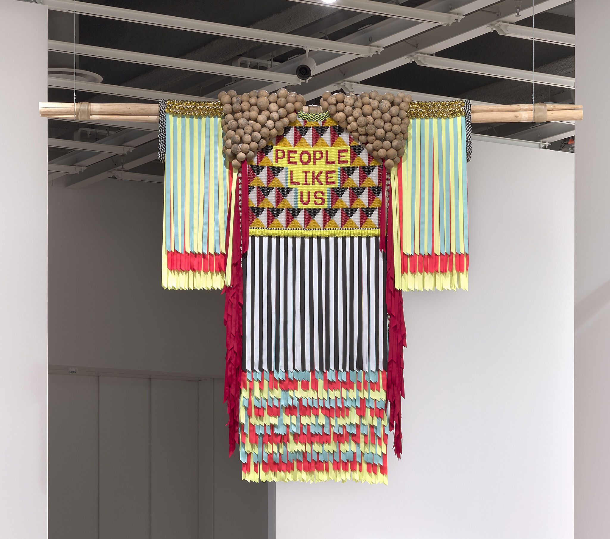 A photograph of a textile sculpture hanging in a gallery.
