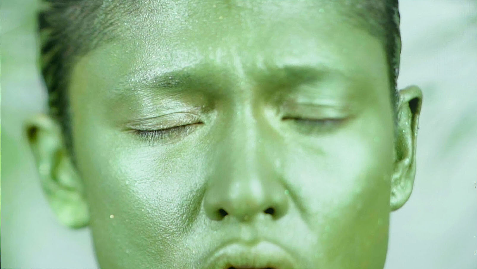 A close up video still of a person's face painted green.