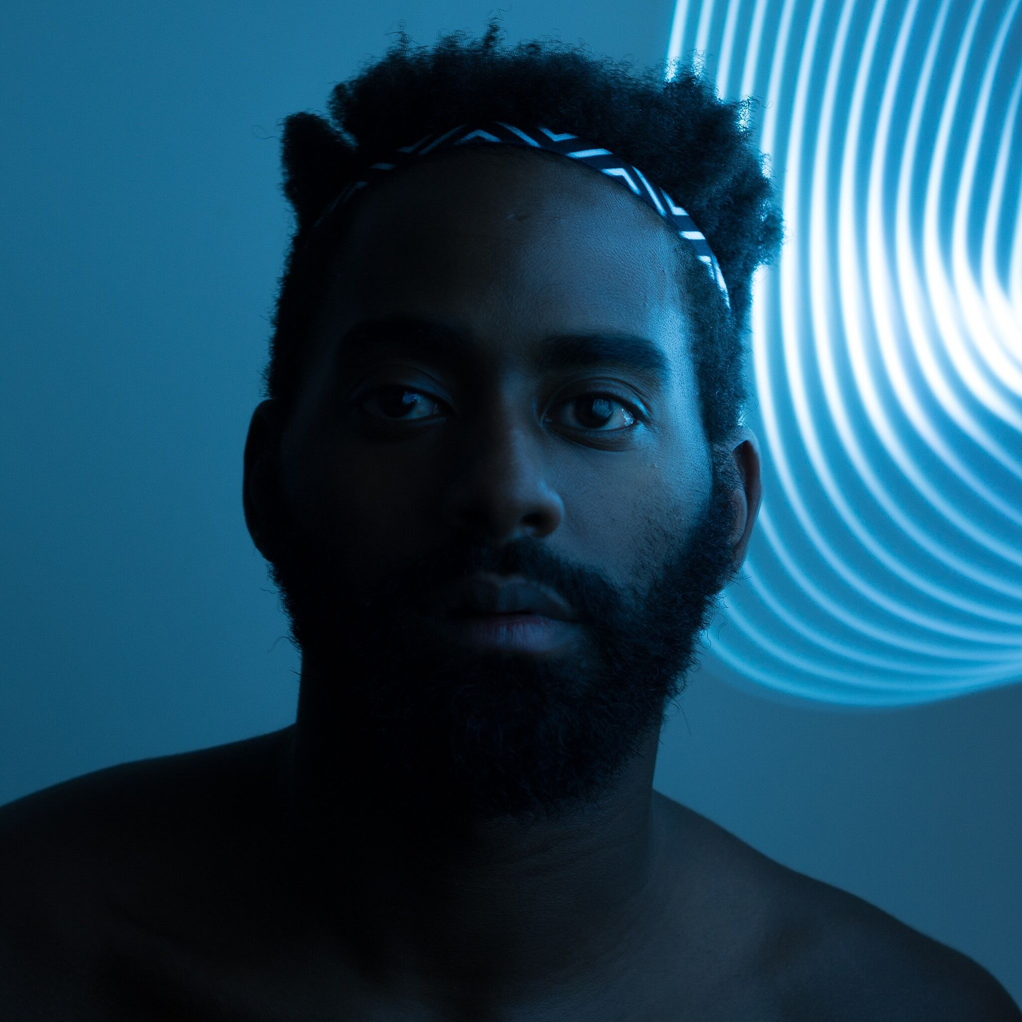 A close up photograph of a person in blue lighting.