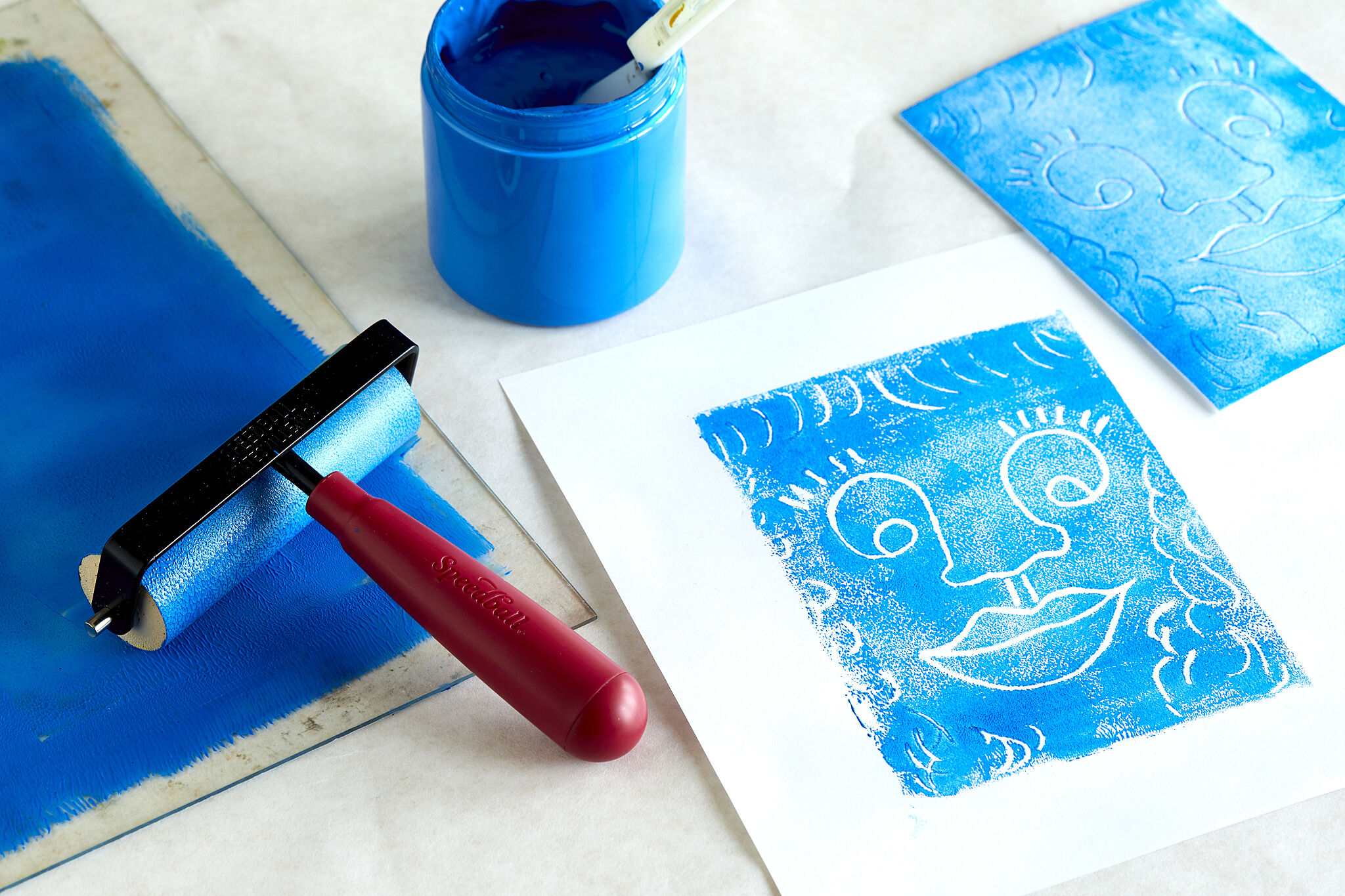 Art tool on a table such as paint, rollers, and paper.