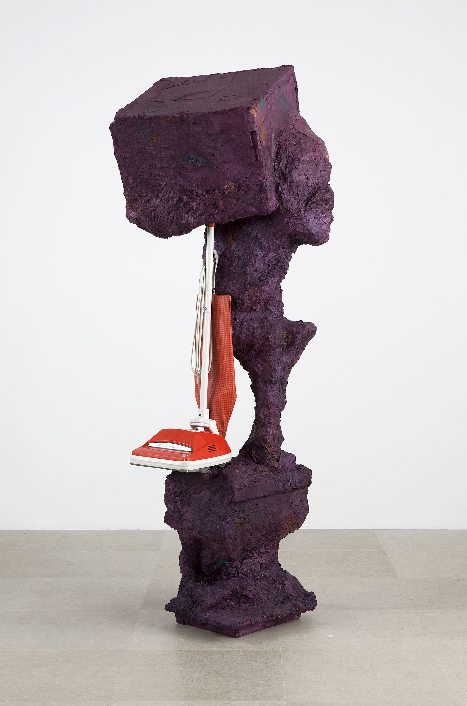 A purple rock-like sculpture holding a red vacuum cleaner.
