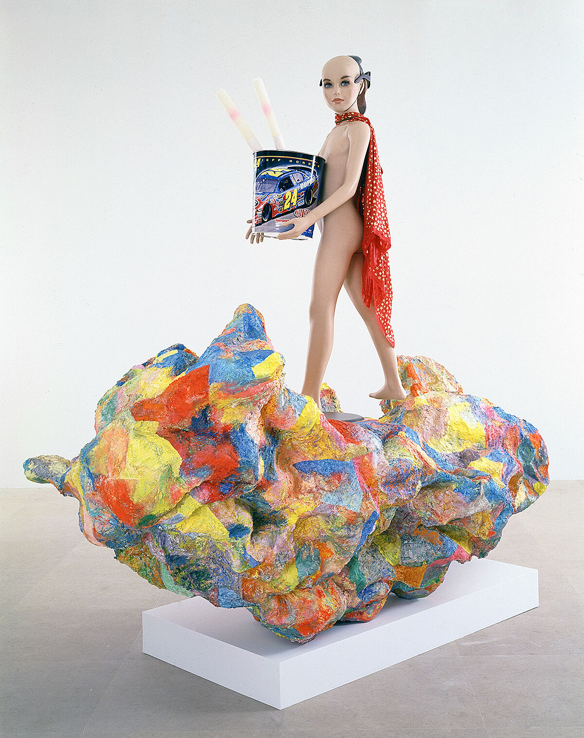 A sculpture of a person standing on a colorful mound wearing a cape and carrying a bucket.