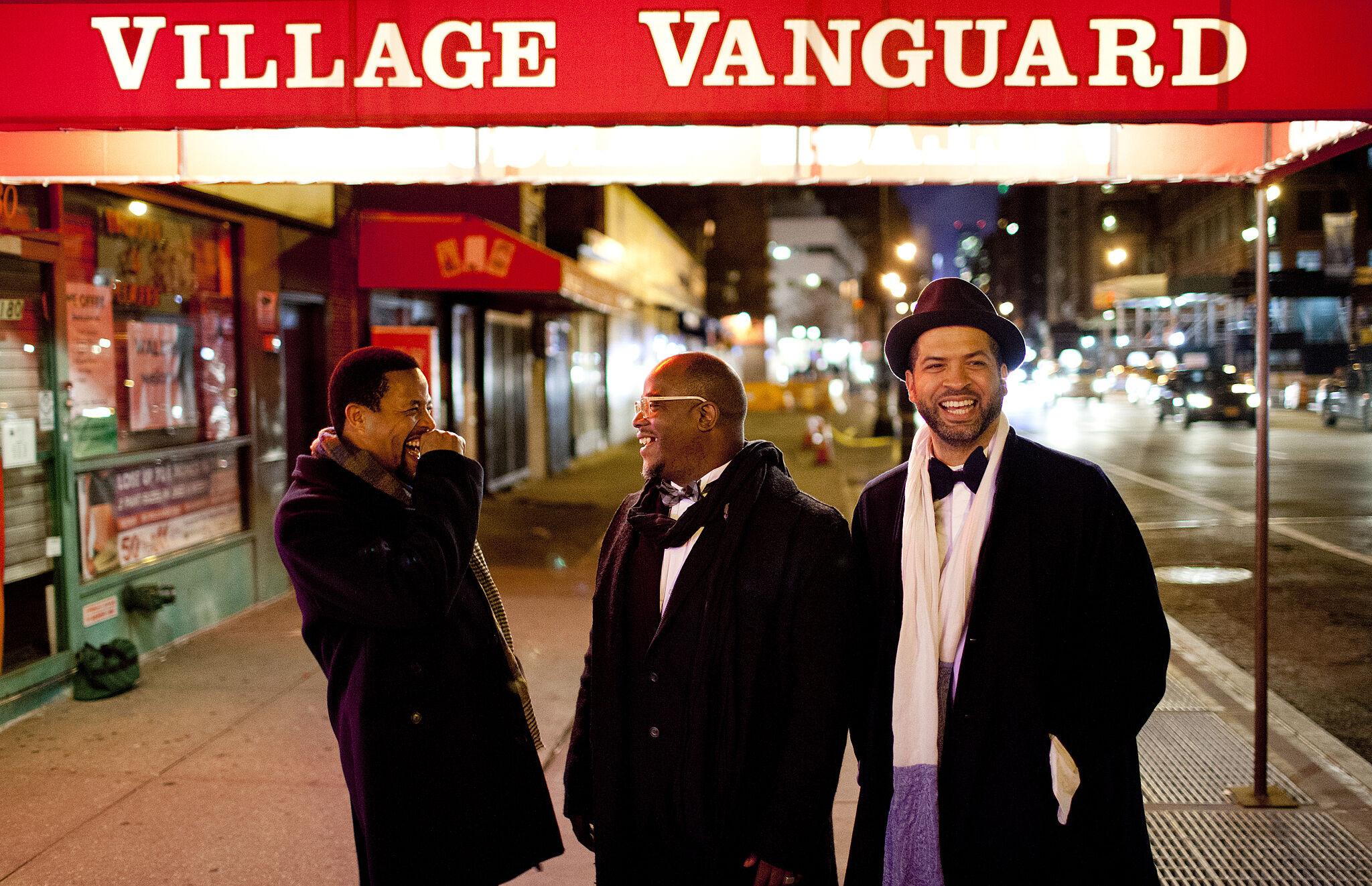 A photo of Nasheet Waits, Tarus Mateen, and Jason Moran outside the Village Vanguard