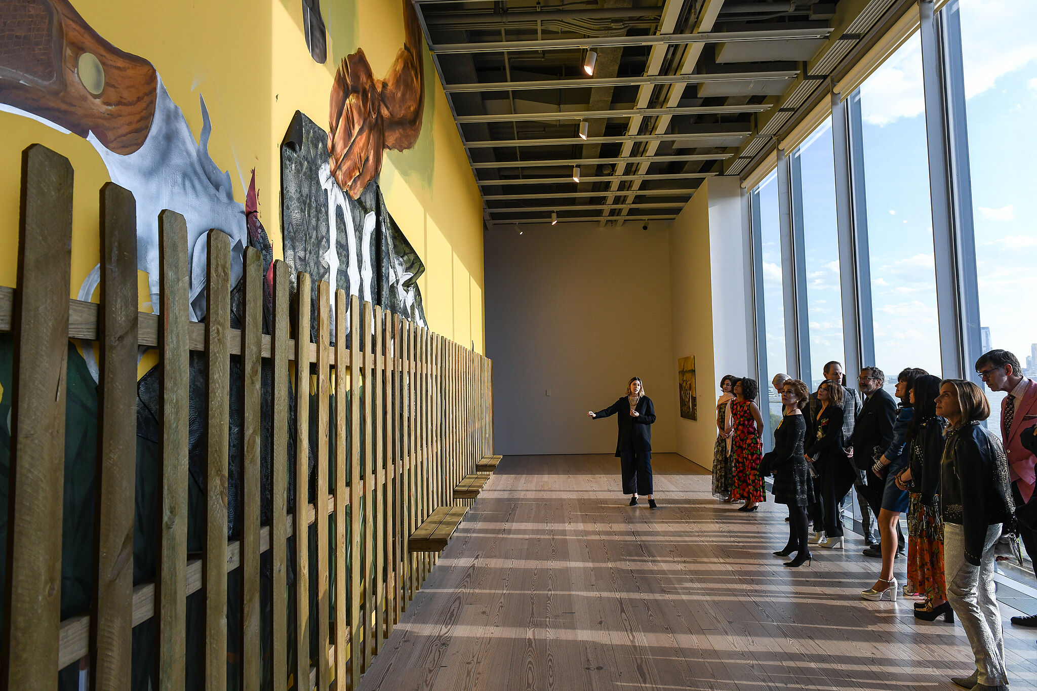 A photo of museum visitors in the gallery viewing the 2019 Whitney Biennial