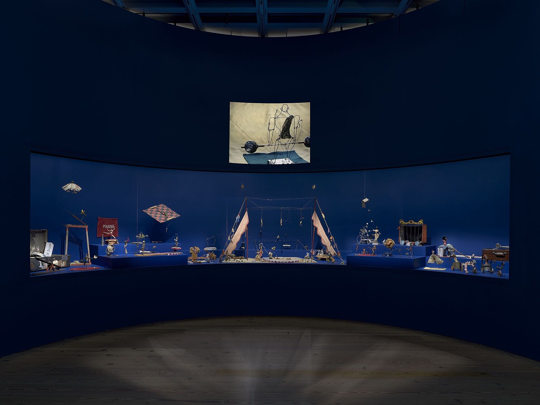 An image of the Whitney galleries with a film projected above a glass enclosure of sculptures