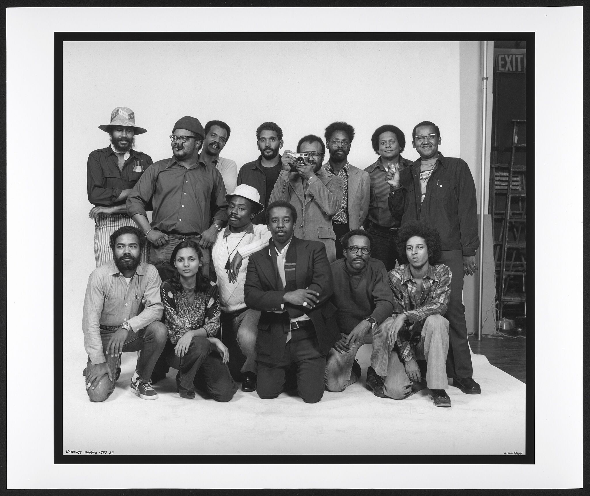 A group of African American artists who are part of the Kamoinge collective posing in front of a white backdrop.