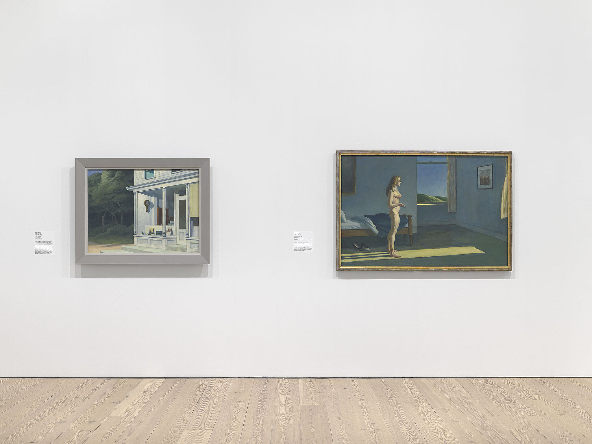 An image of the Whitney galleries with two paintings on the wall