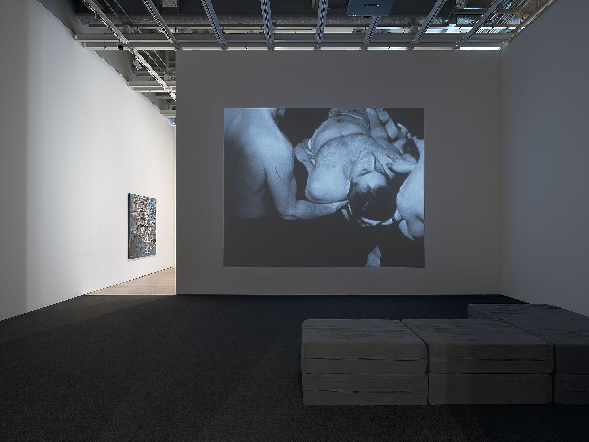 An image of the Whitney galleries with a video projected on the wall