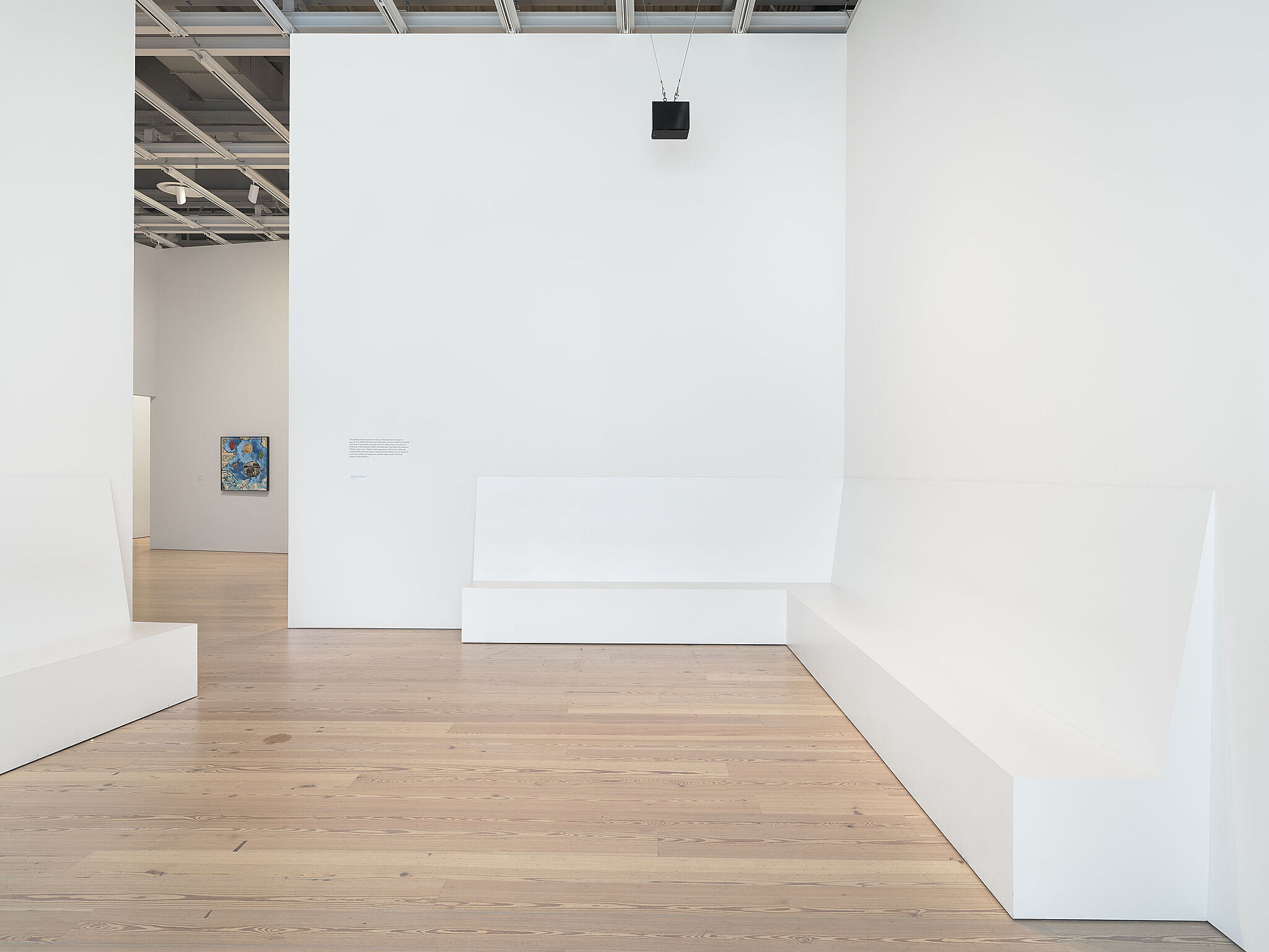 An image of the Whitney galleries with a small speaker on the wall