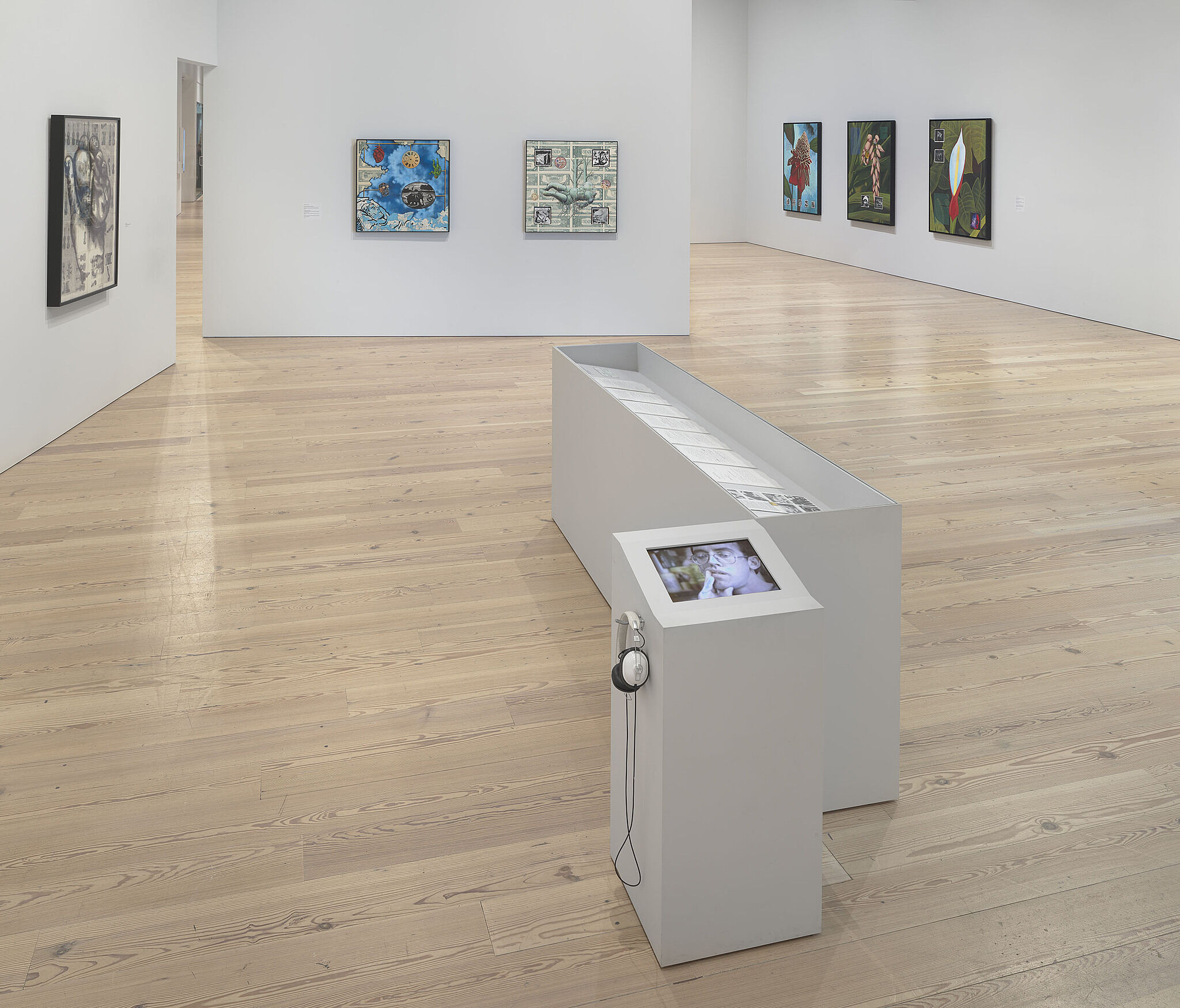 An image of the Whitney galleries with various artworks on the wall and vitrines