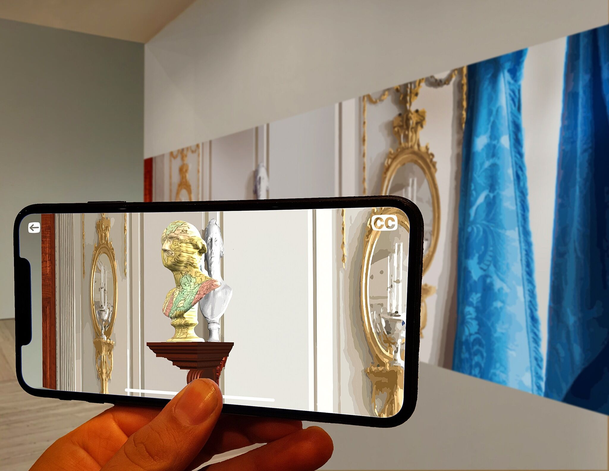 An image of a phone being held up in front of artwork on the wall