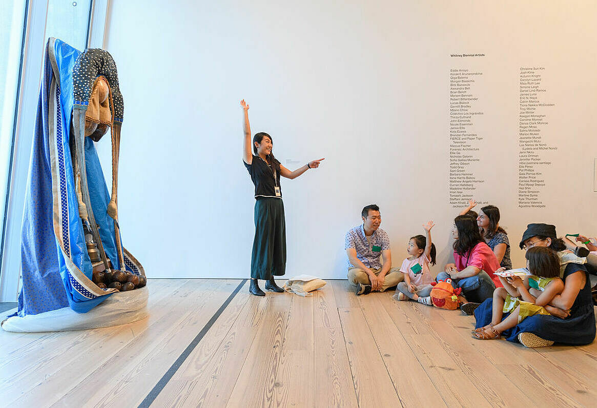 A photo of a person in the Whitney galleries speaking in front of a group of families