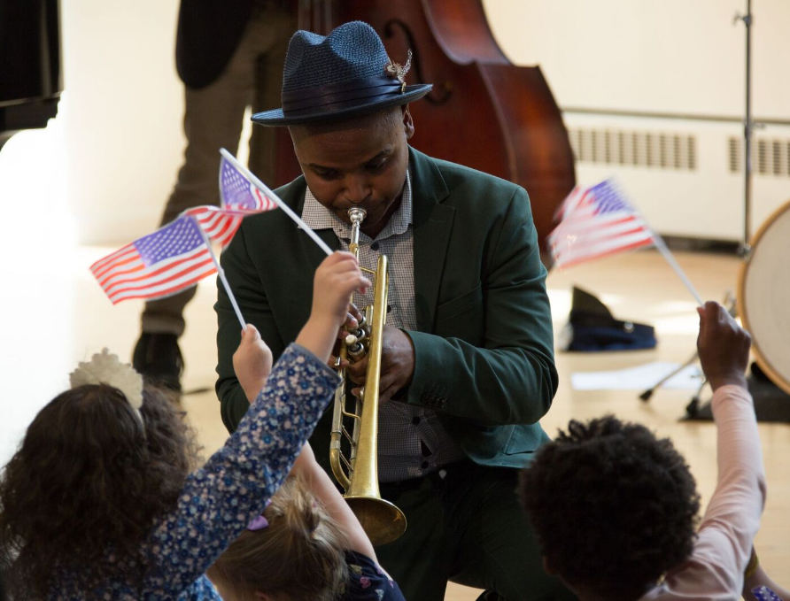 A photo of a person playing the trumpet surrounded by children waving American flags.